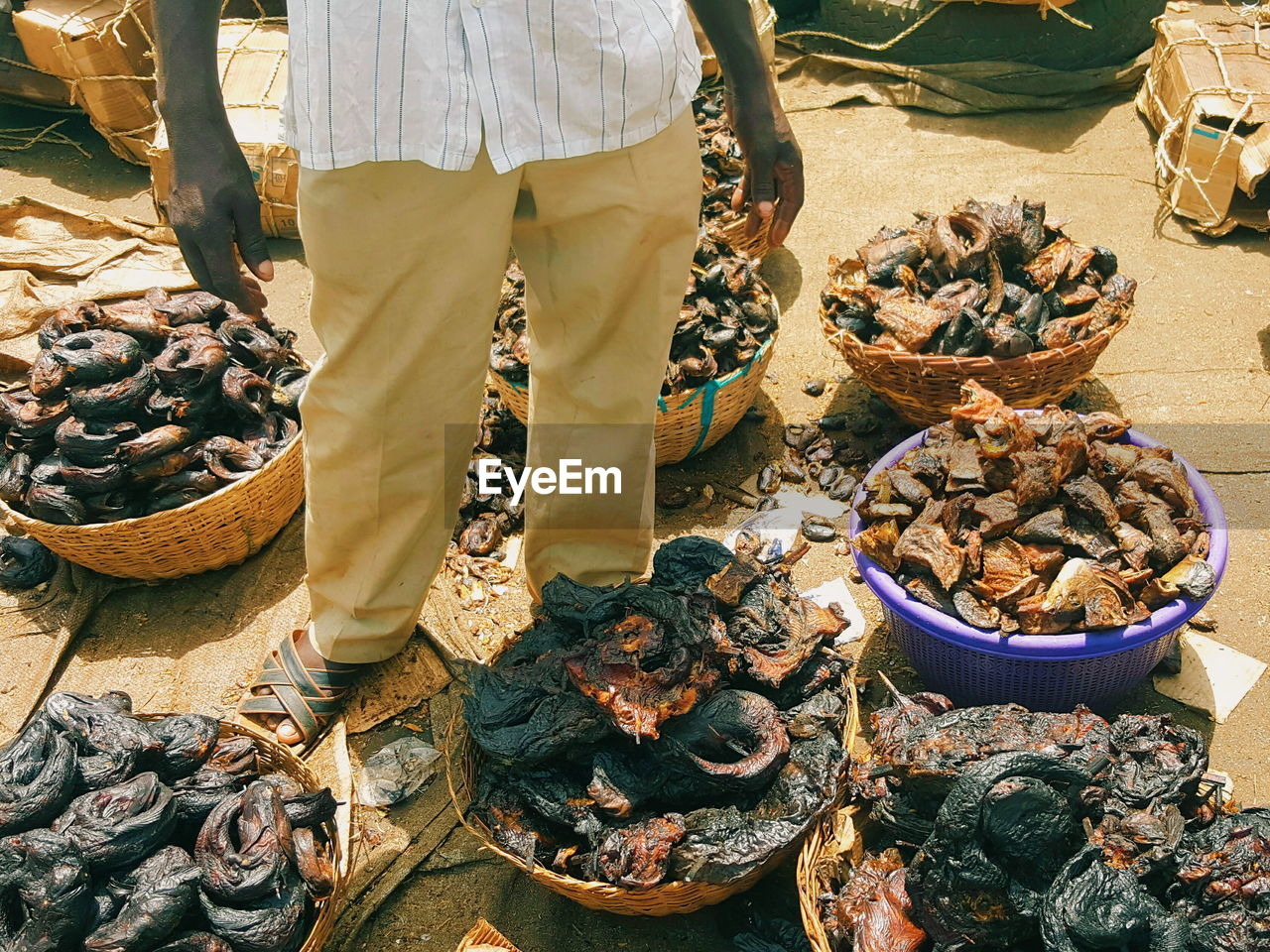 Low Section Of Man With Smoked Fish For Sale At Market