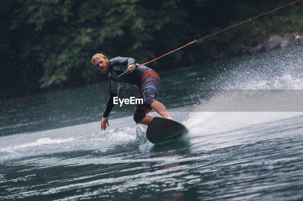 Full length of man splashing water in river