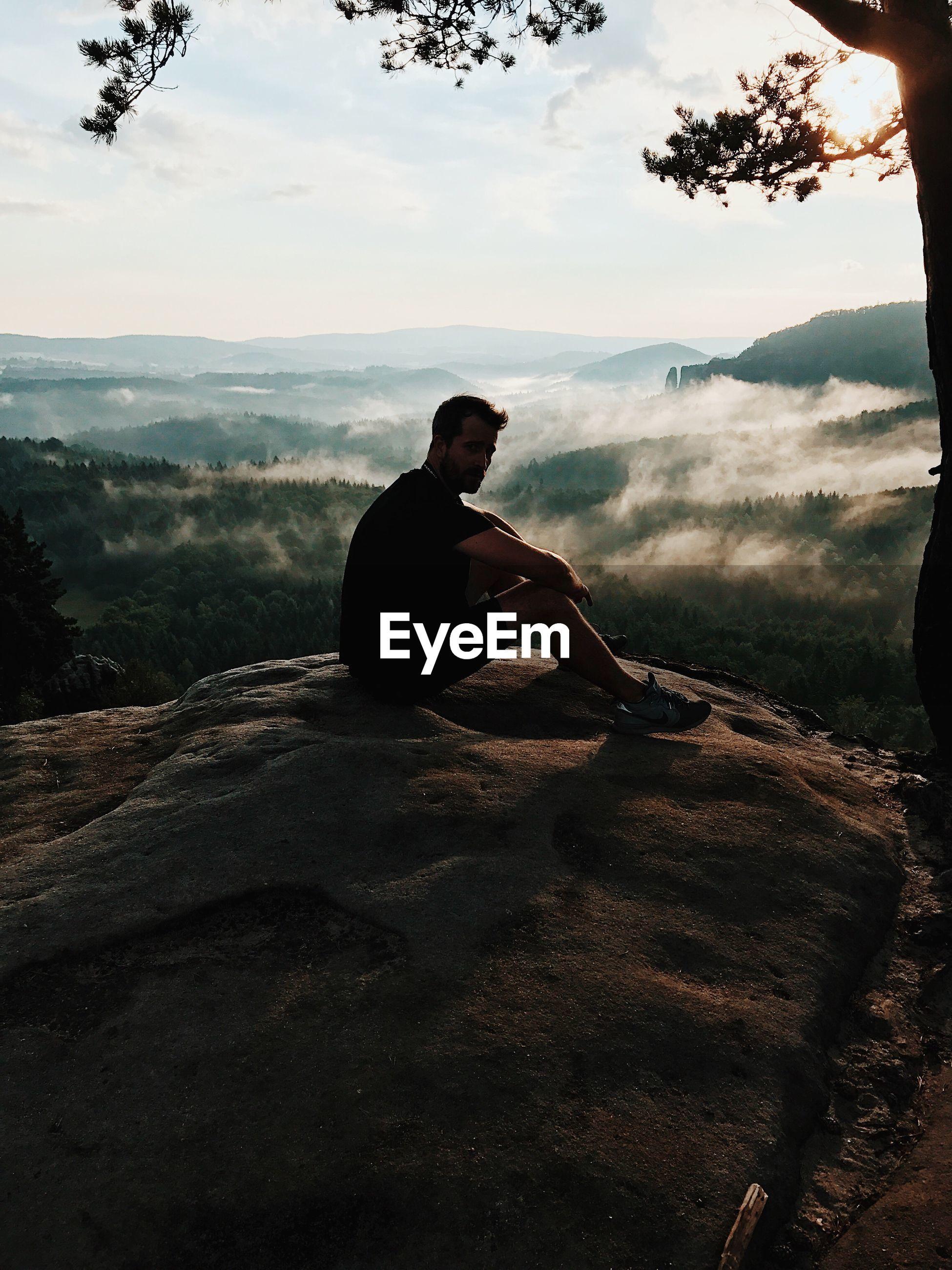 MAN SITTING ON LANDSCAPE AGAINST MOUNTAIN RANGE
