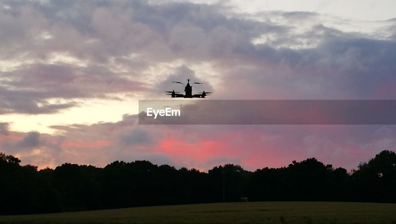 cloud - sky, transportation, sky, flying, sunset, mode of transport, air vehicle, airplane, no people, tree, nature, low angle view, outdoors, beauty in nature, day