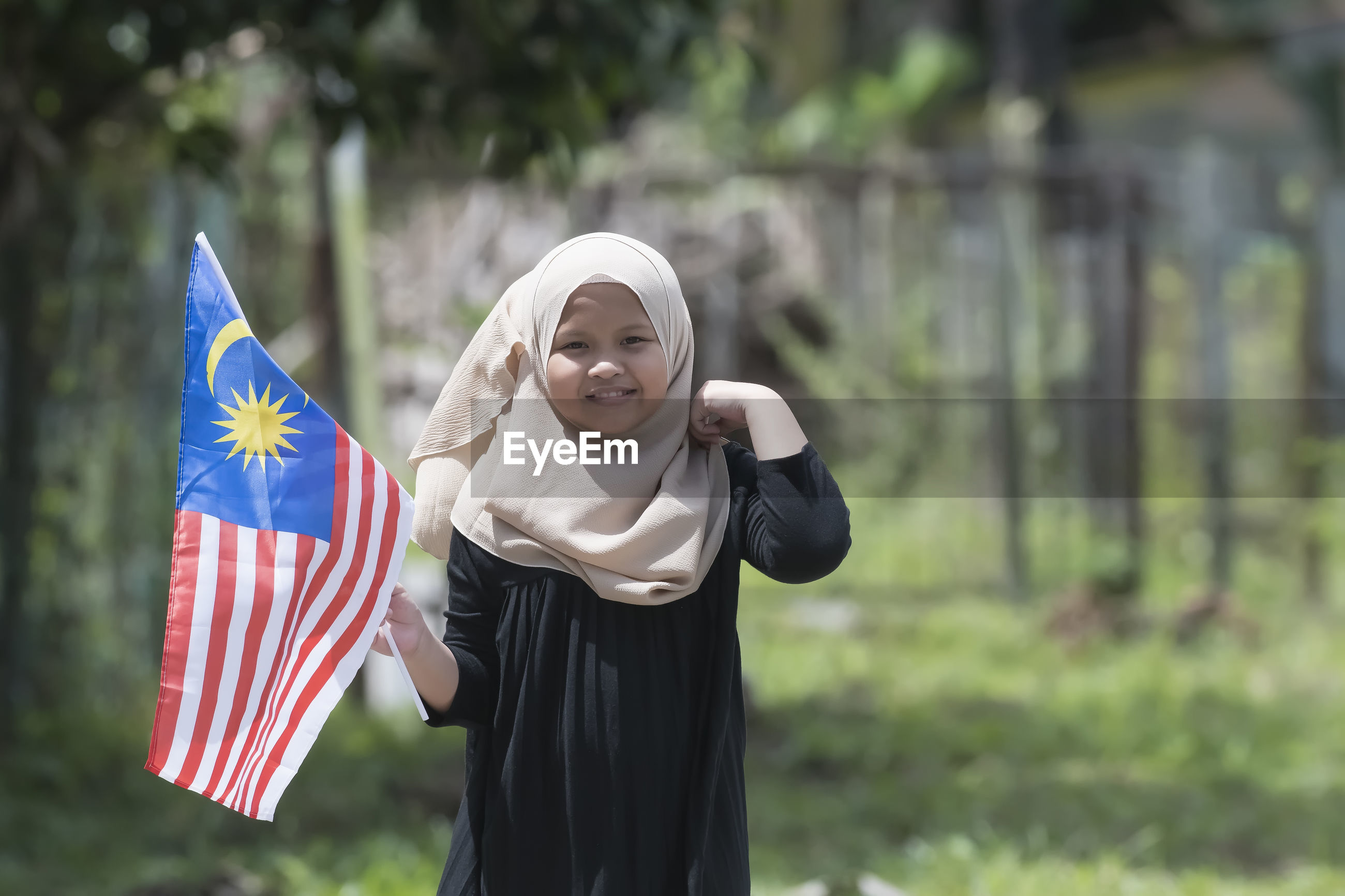 Portrait of girl in hijab holding malaysian flag while standing at field