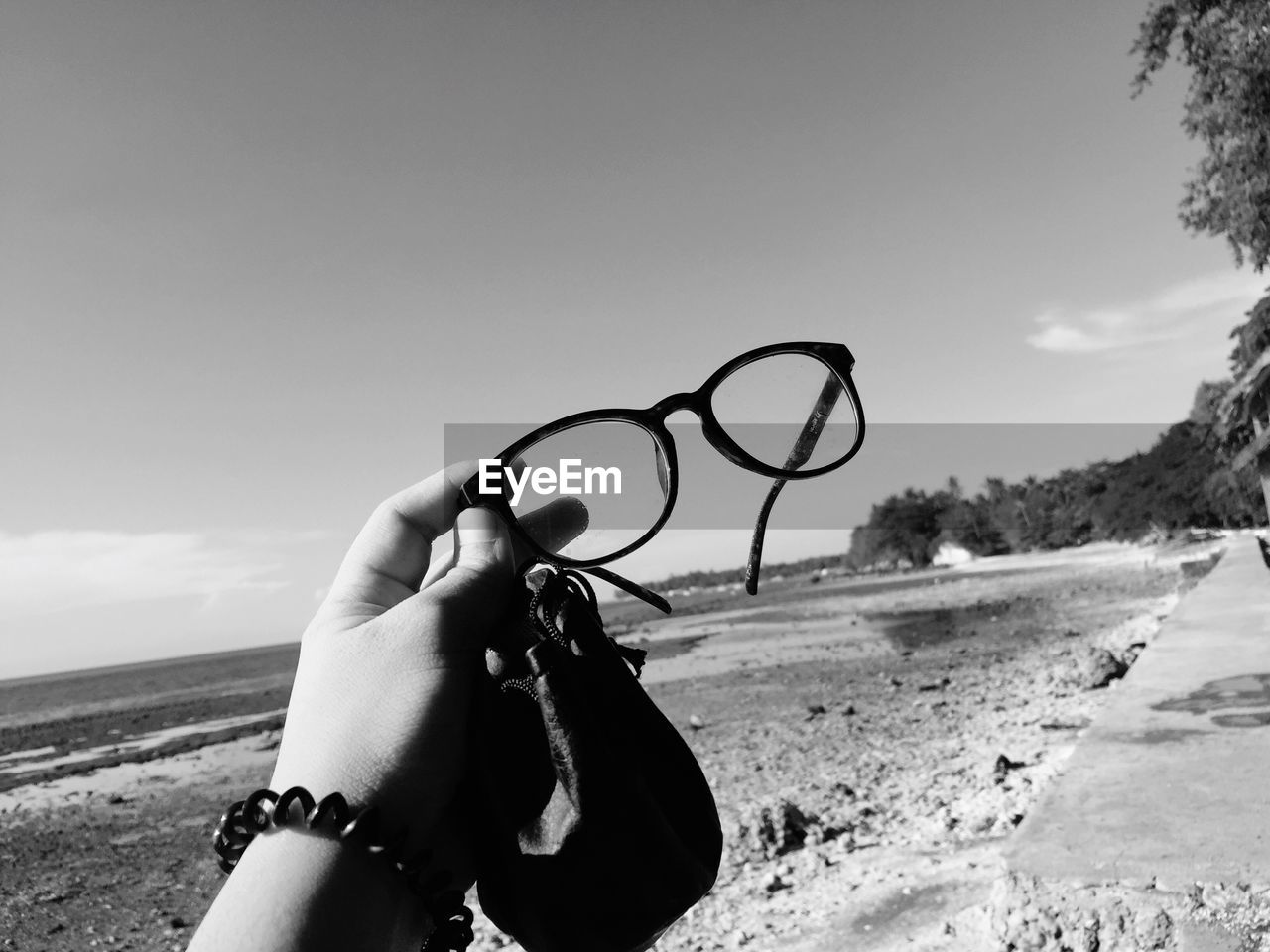 sky, human hand, hand, real people, one person, holding, glasses, land, nature, human body part, personal perspective, lifestyles, leisure activity, day, beach, unrecognizable person, eyeglasses, finger, human finger, outdoors, personal accessory