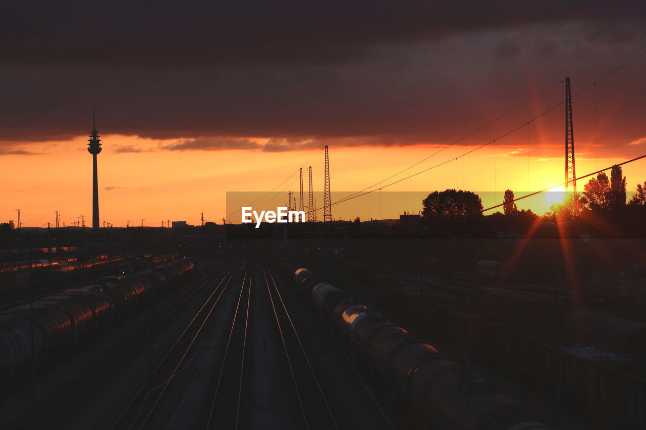 sunset, sky, rail transportation, transportation, railroad track, track, orange color, nature, cloud - sky, architecture, mode of transportation, silhouette, no people, connection, public transportation, sun, built structure, train, train - vehicle, outdoors, electricity
