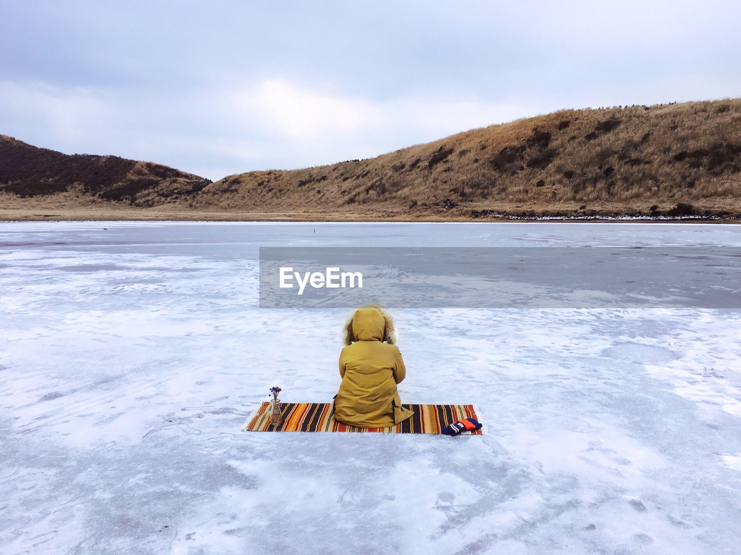 Rear view of a person sitting on frozen lake