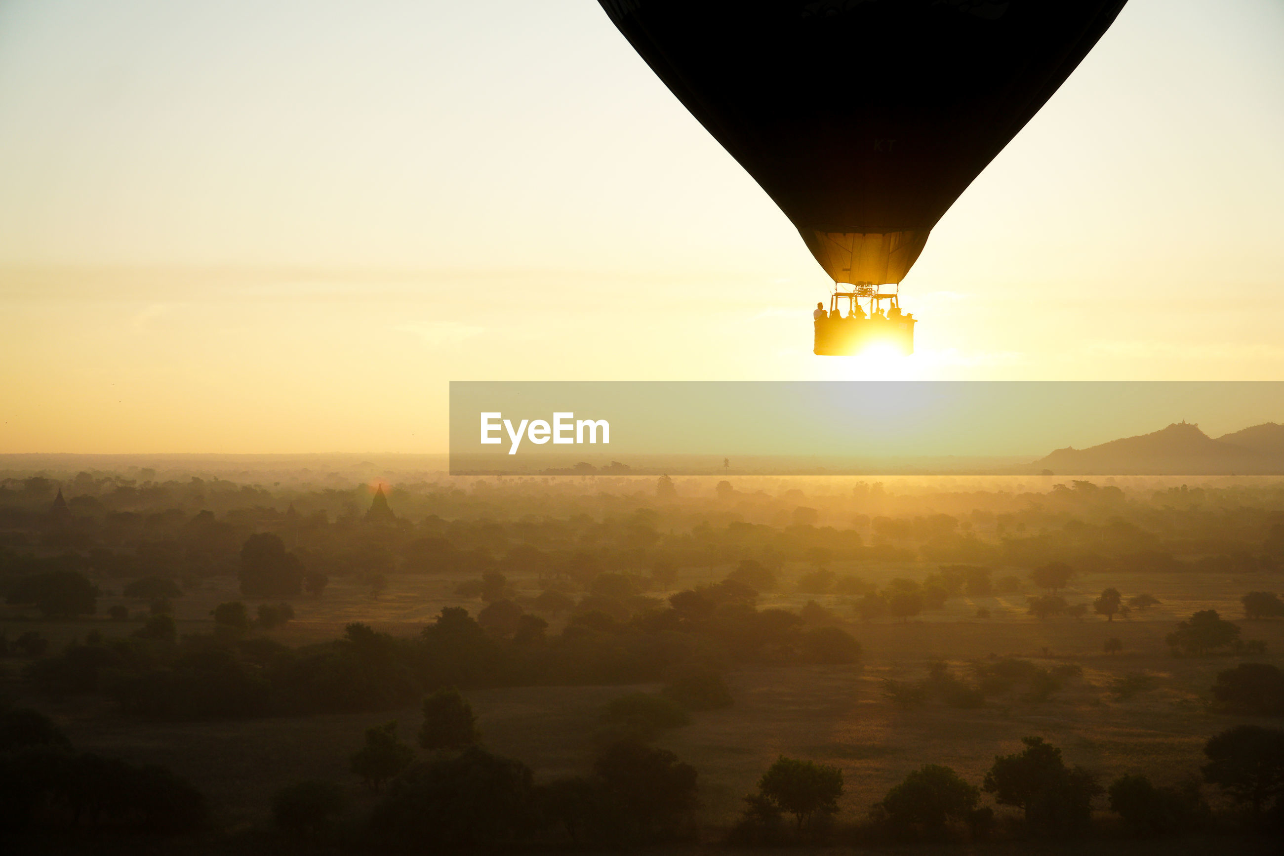 Scenic view of hot air balloon landscape against sky during sunrise