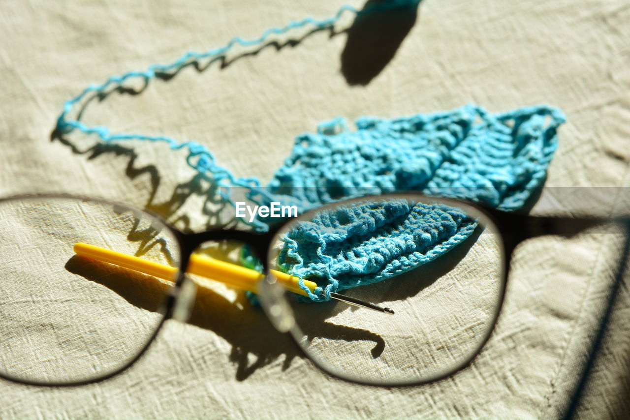Close-up of wool with knitting needle and eyeglasses on table