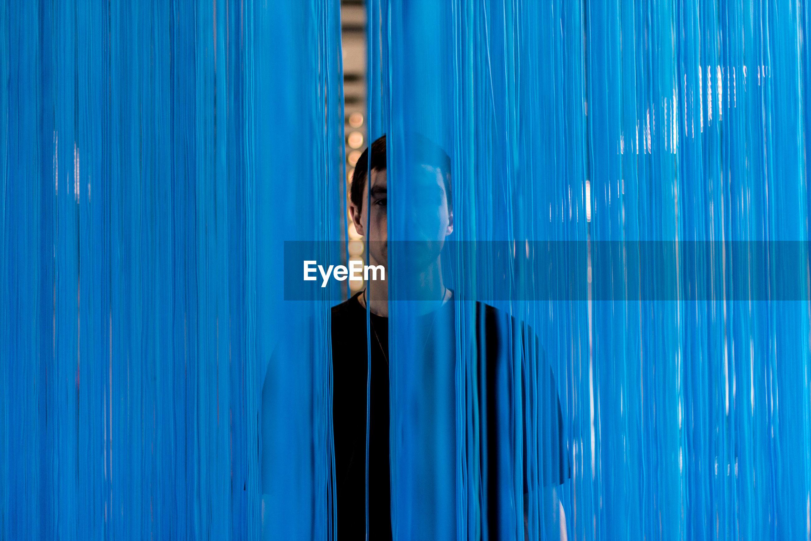 Portrait of man standing behind blue textile