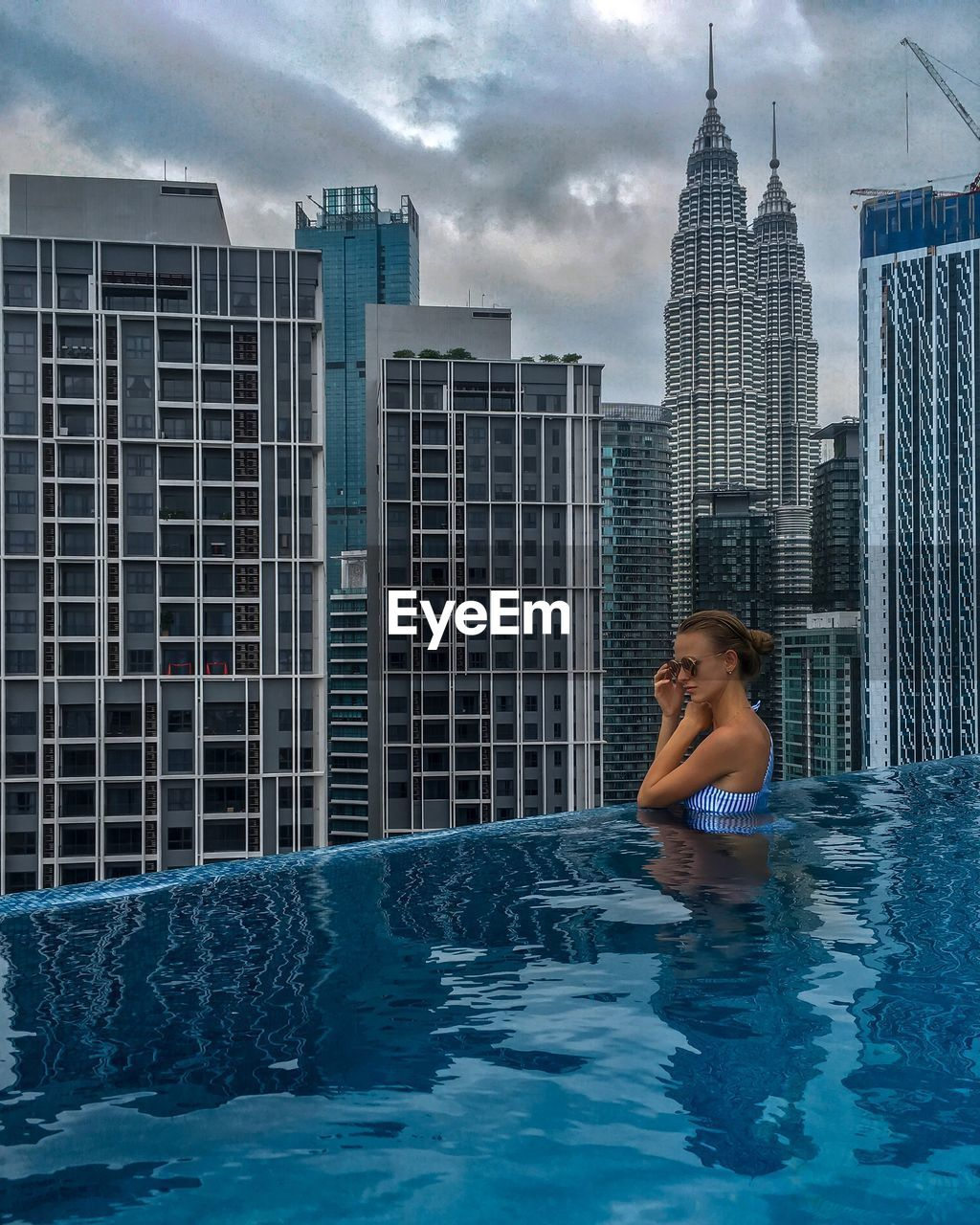 Full Woman At Infinity Pool Against Modern Building In City