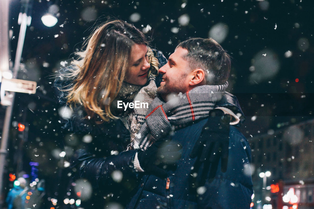 Couple Romancing While Standing Against Sky At Night During Winter