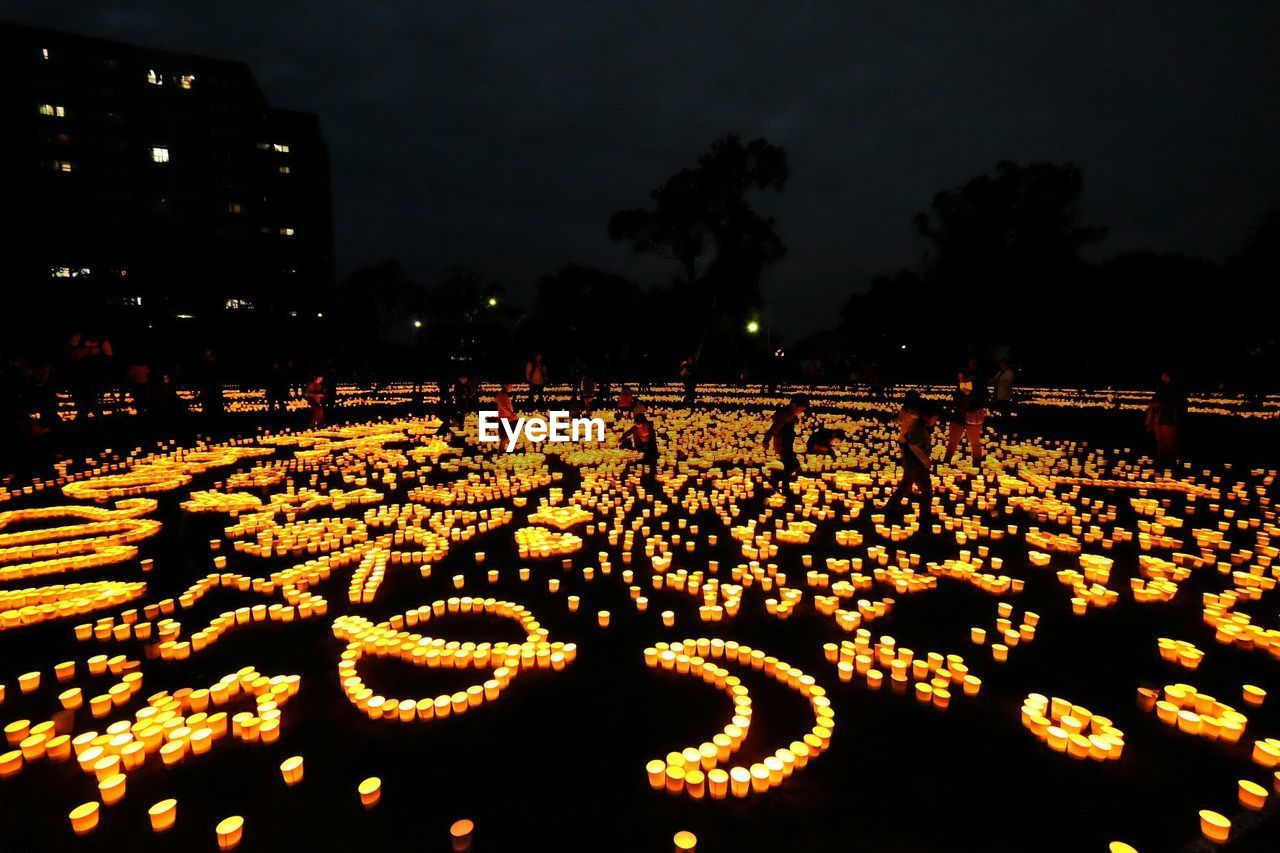 Children Surrounded By Lit Candles At Night