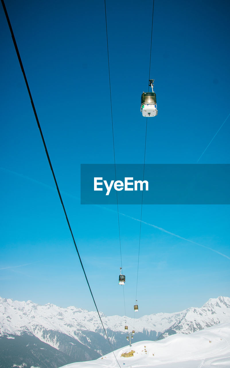 cable car, snow, winter, mountain, overhead cable car, cable, sky, blue, ski lift, cold temperature, scenics - nature, beauty in nature, nature, mountain range, low angle view, adventure, hanging, travel, snowcapped mountain, no people, outdoors, electricity, mountain peak