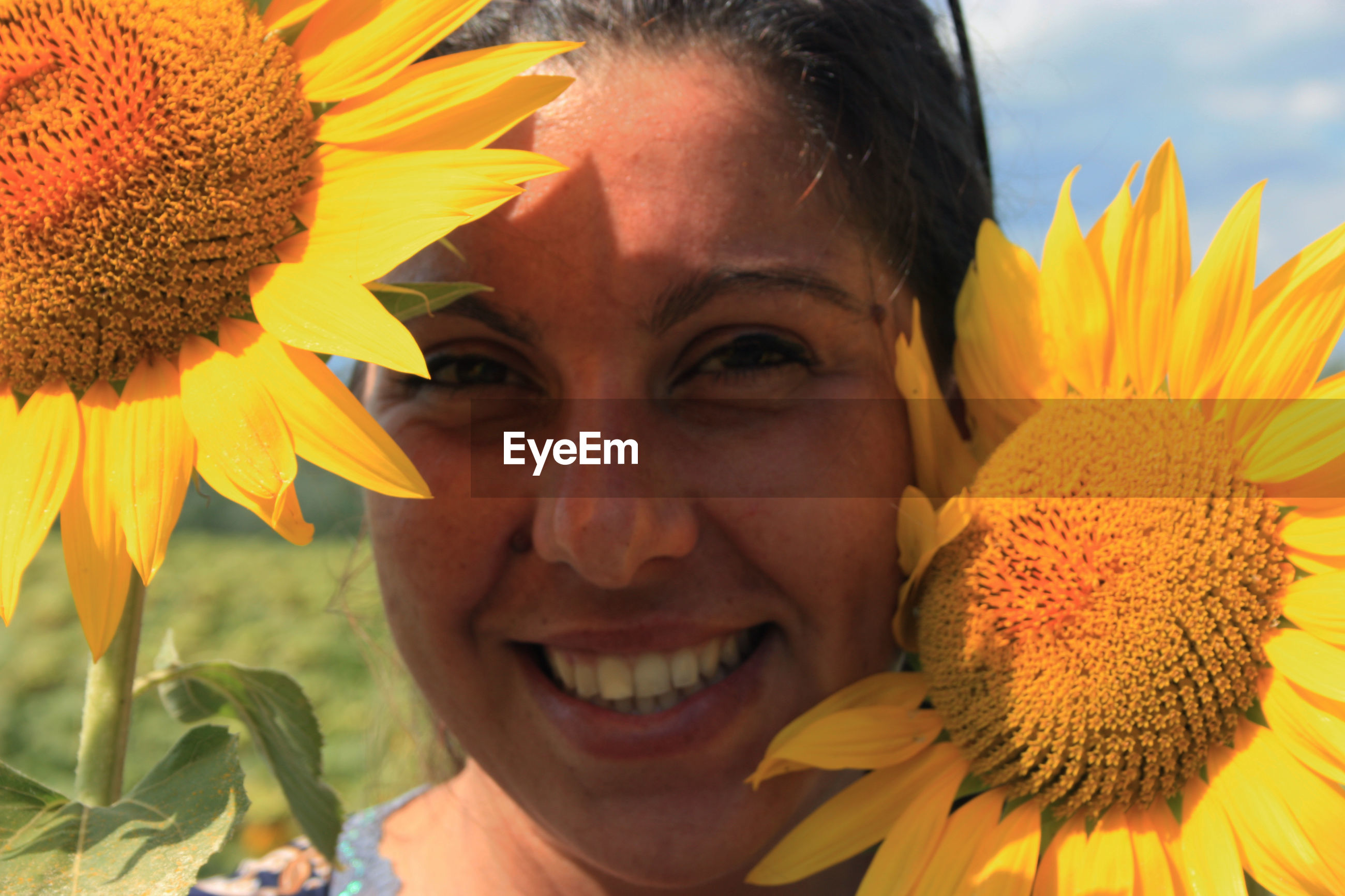 CLOSE-UP PORTRAIT OF A SMILING YOUNG WOMAN WITH SUNFLOWER