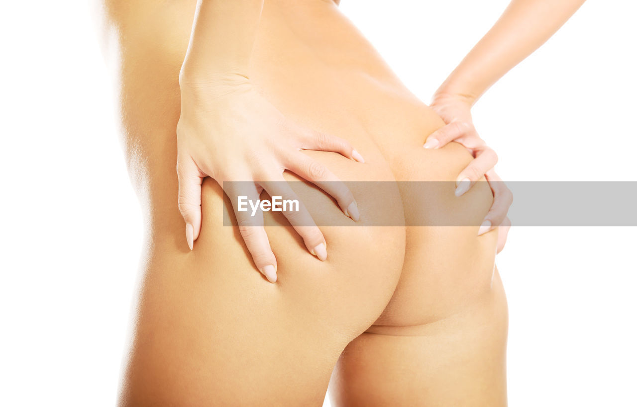 Close-up of woman touching buttocks while standing against white background