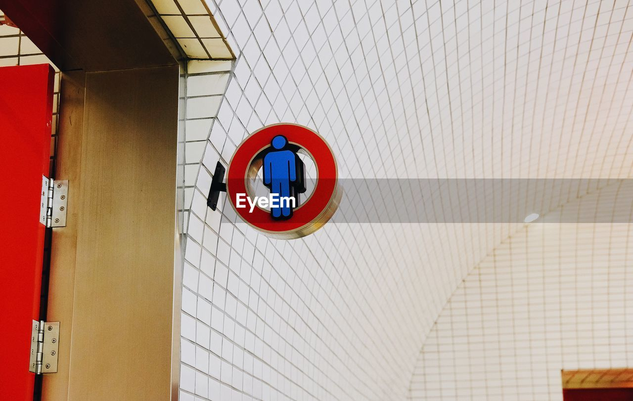 Low Angle View Of Sign On White Tiled Wall