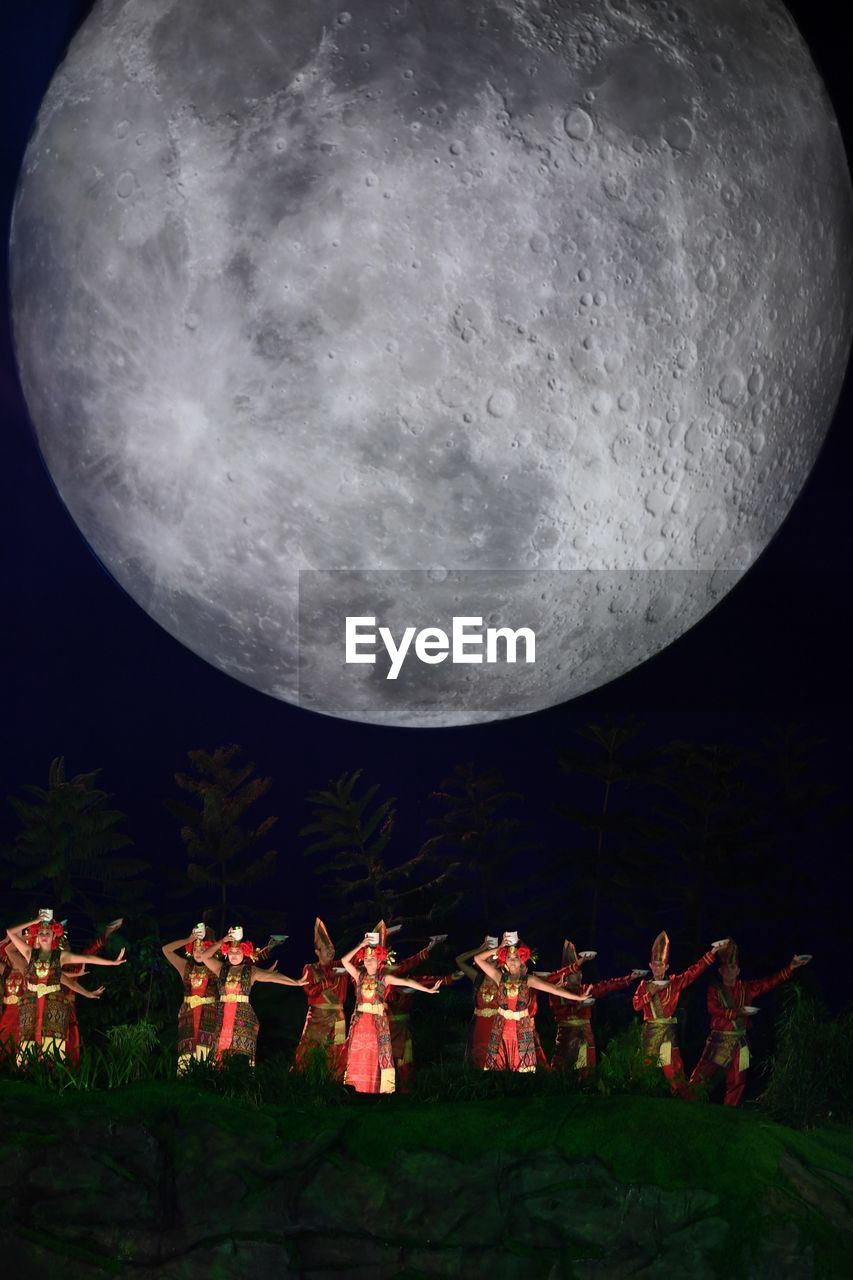 night, moon, sky, nature, group of people, full moon, astronomy, arts culture and entertainment, space, outdoors, real people, celebration, people, traditional clothing, field, togetherness, moonlight, festival