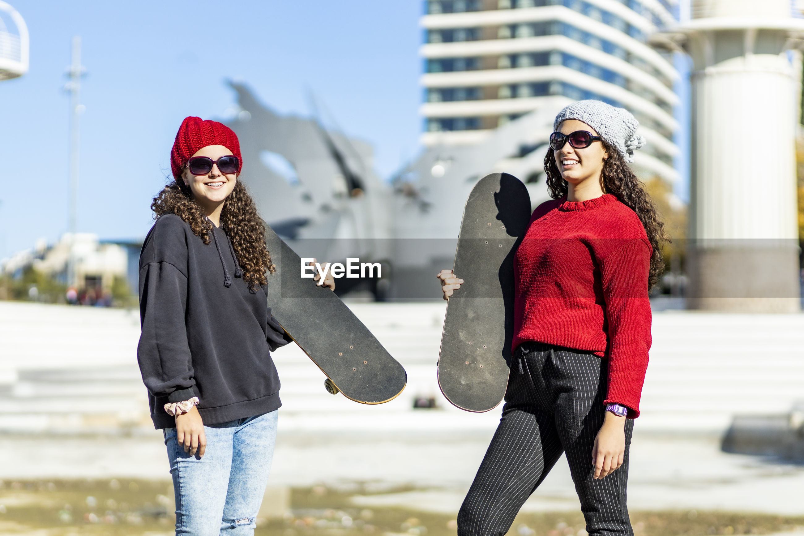 Teenage girls with skateboard standing in city