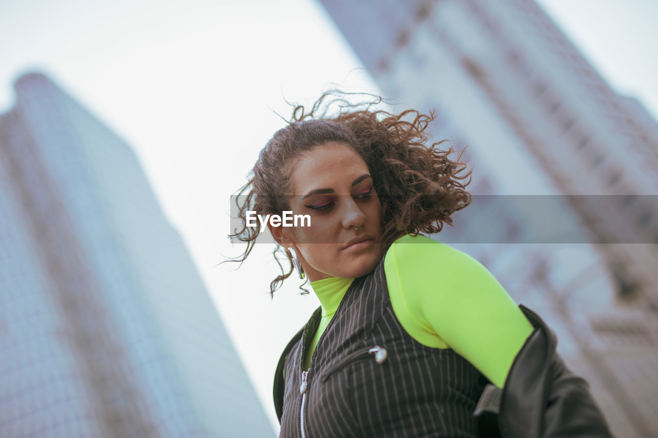 real people, portrait, one person, headshot, lifestyles, curly hair, leisure activity, young adult, day, hairstyle, young women, casual clothing, focus on foreground, hair, front view, clothing, standing, looking, outdoors, warm clothing