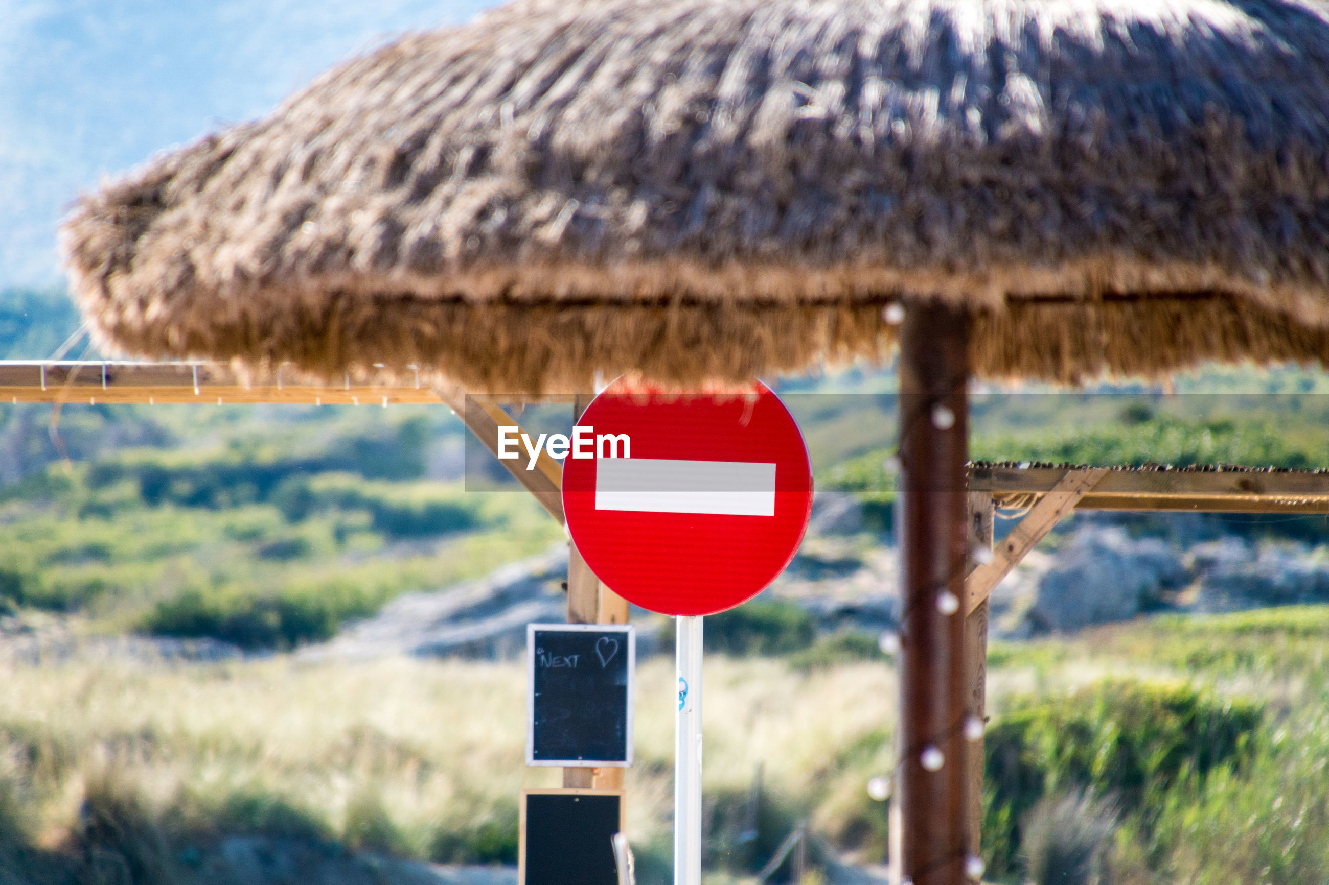 Thatched roof against do not enter sign on field