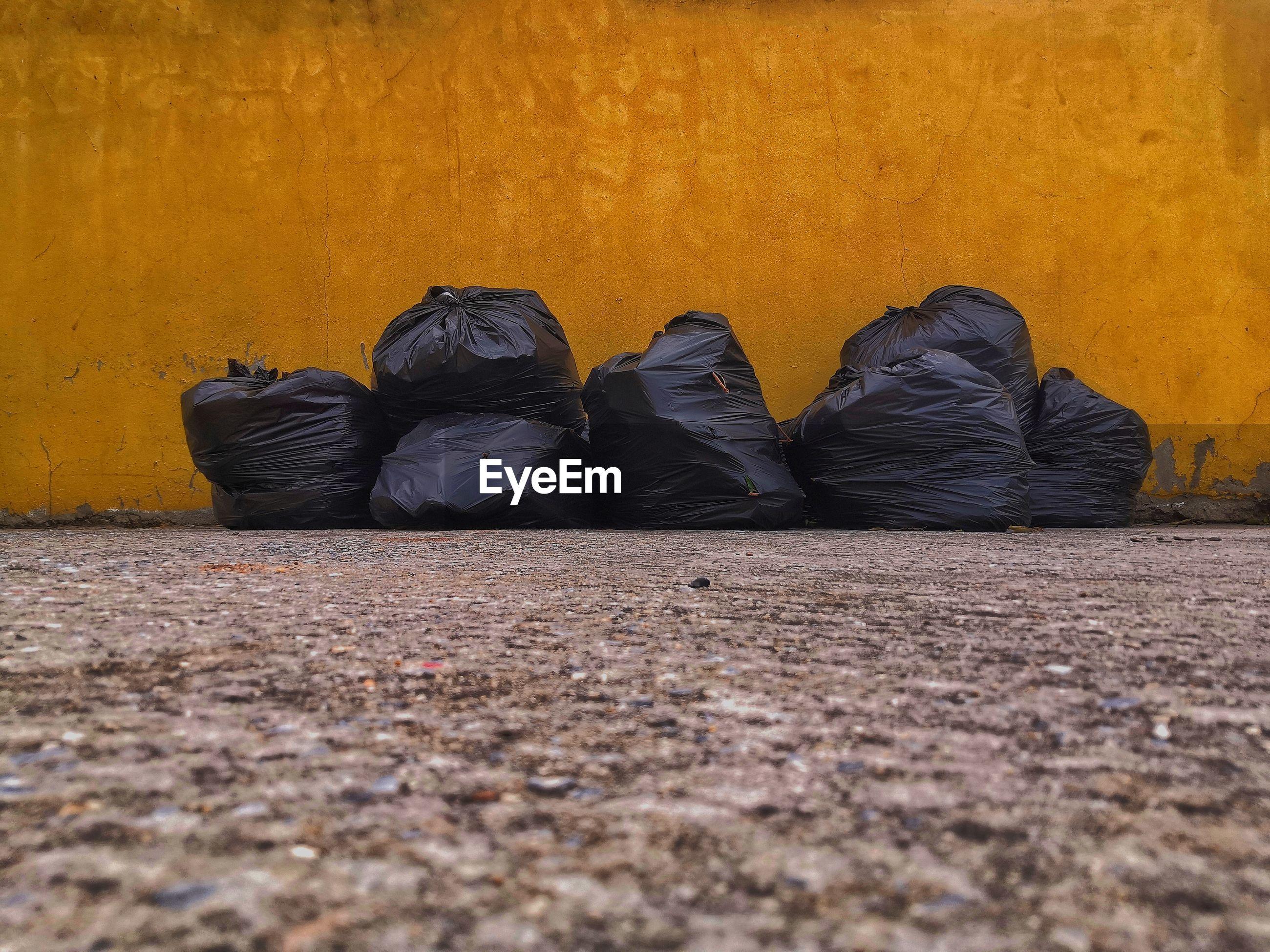 Black bag garbage dump beside the wall
