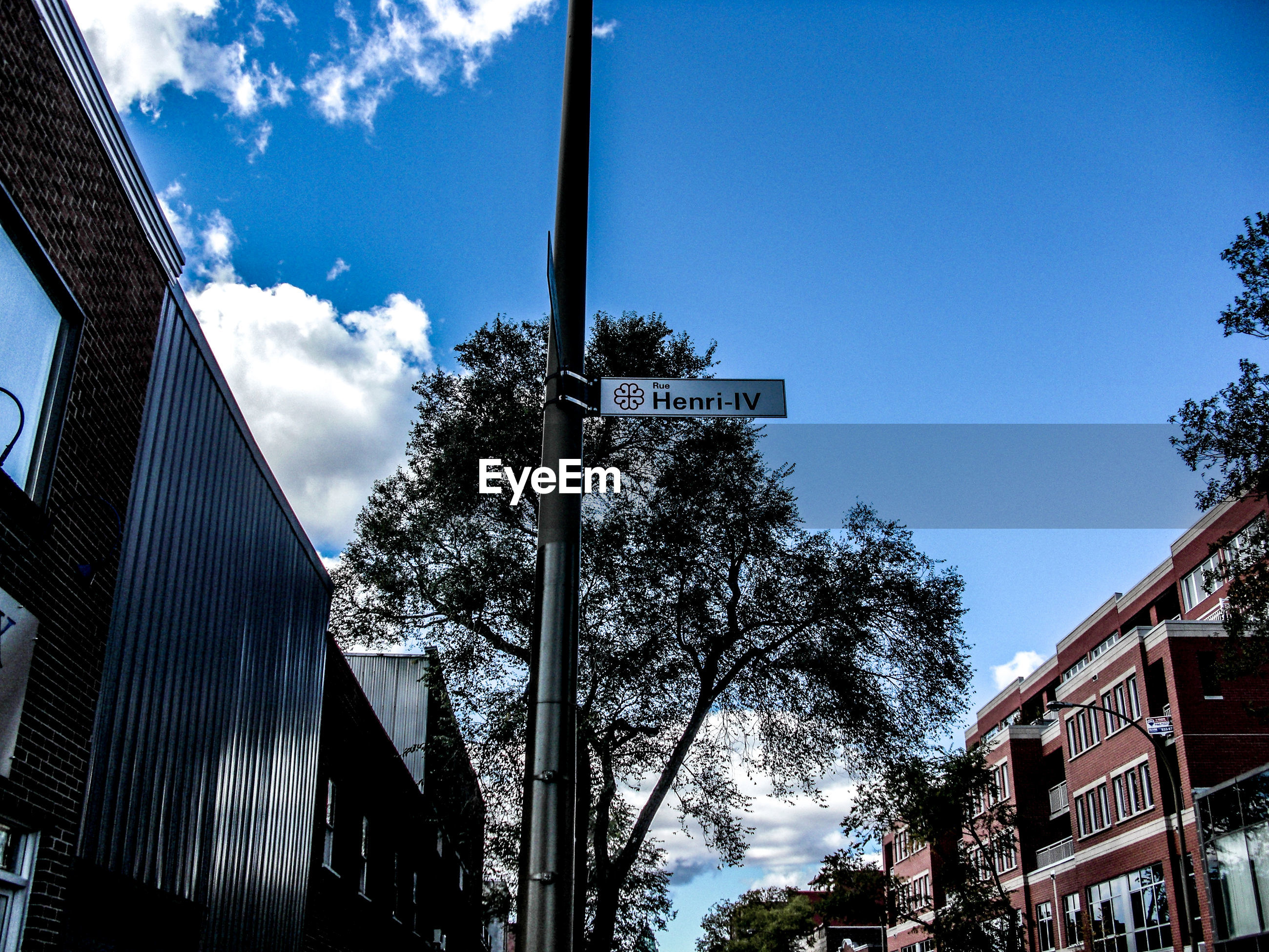 Low angle view of information sign by building against sky in city