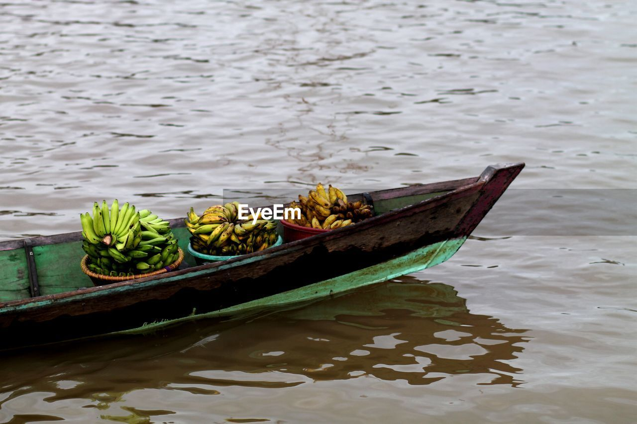 water, nautical vessel, mode of transportation, transportation, waterfront, lake, no people, day, high angle view, nature, outdoors, healthy eating, container, wood - material, reflection, floating, floating on water, freshness, rowboat