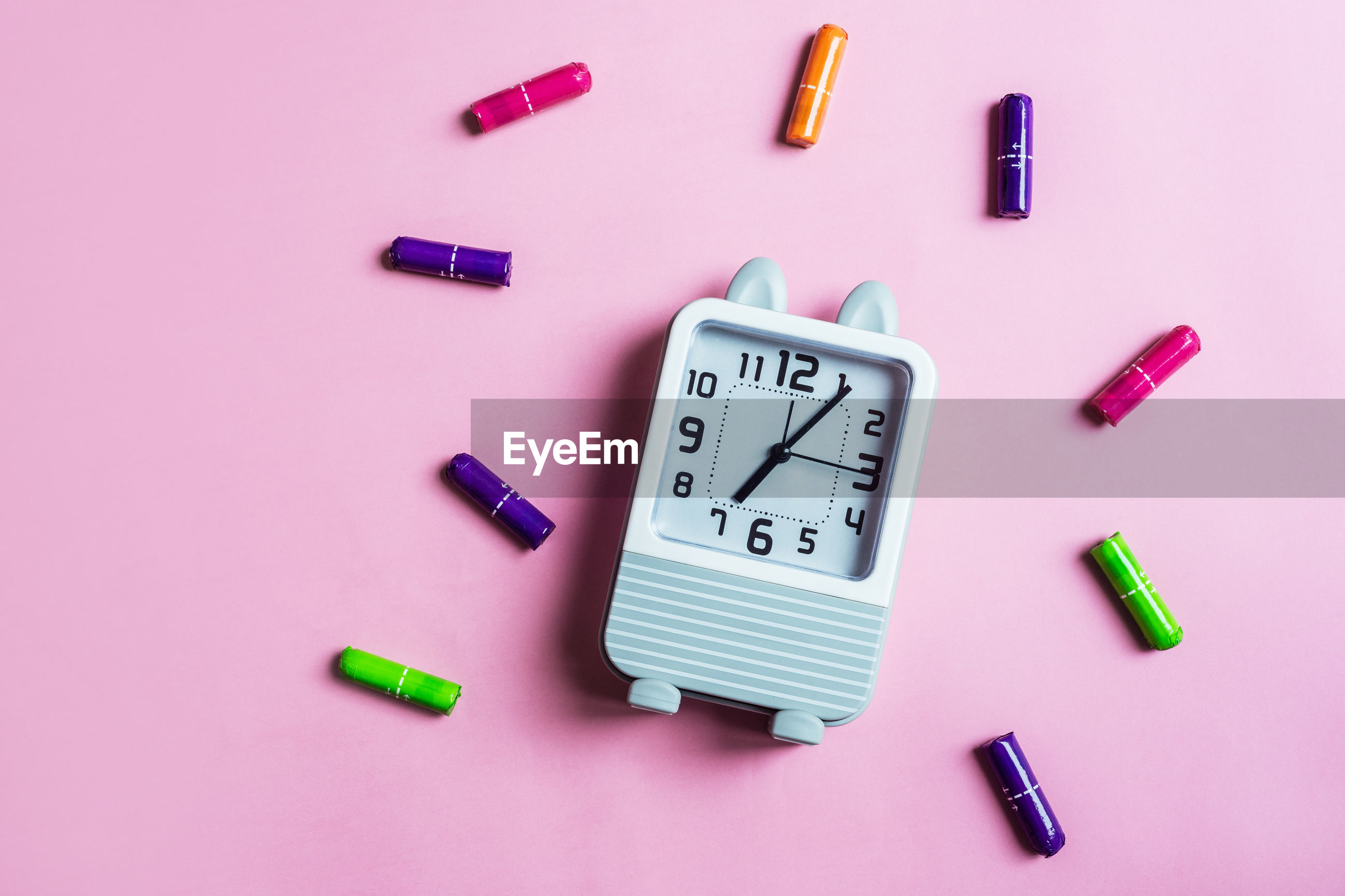 High angle view of clock with crayons on pink background