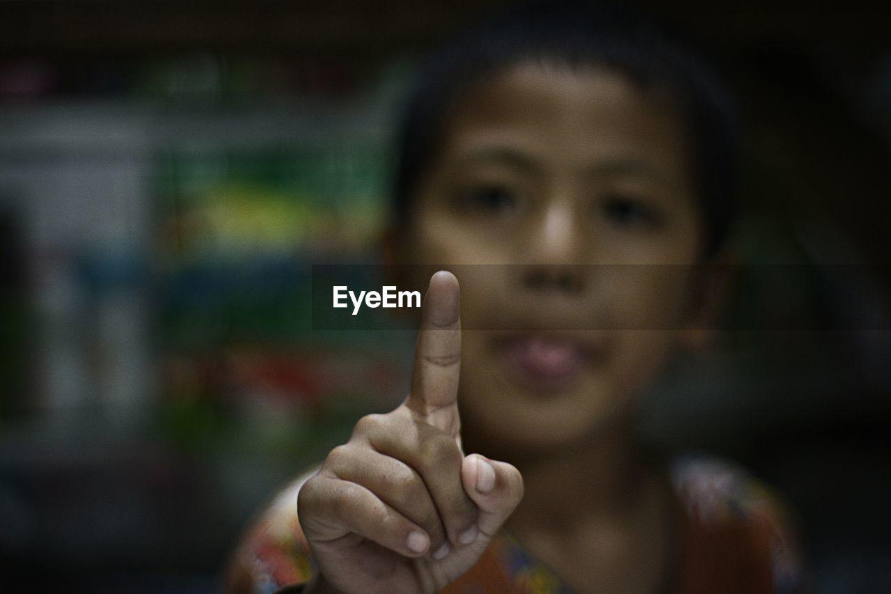 Close-up of boy pointing at camera
