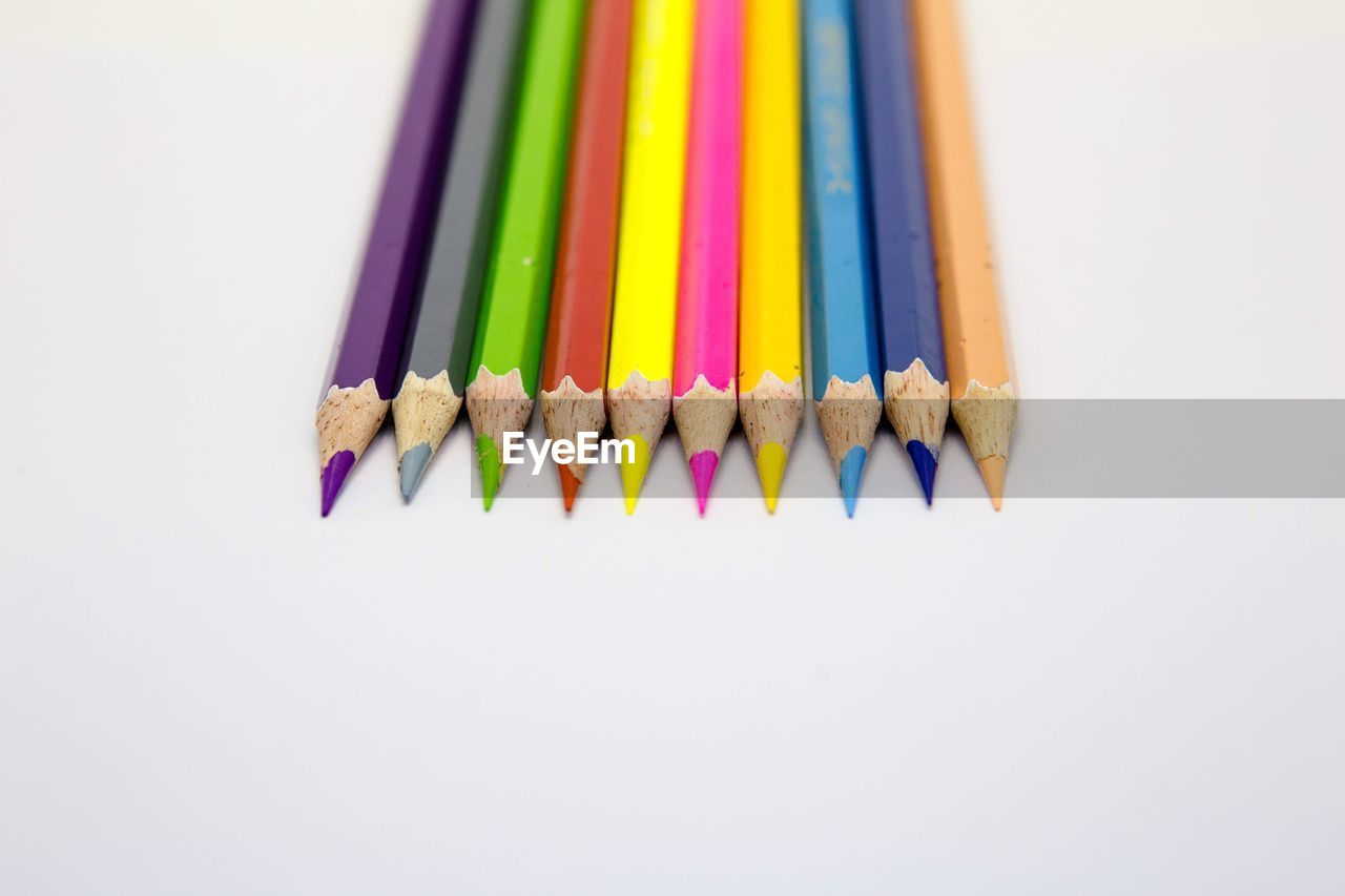 colored pencil, white background, multi colored, still life, pencil, variation, studio shot, variety, choice, wood - material, no people, close-up, pencil sharpener, large group of objects, pencil shavings