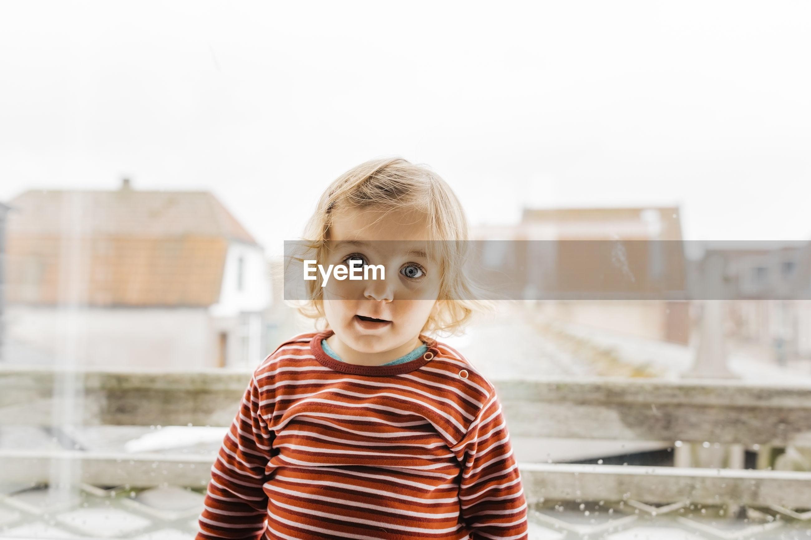 Portrait of cute girl against houses