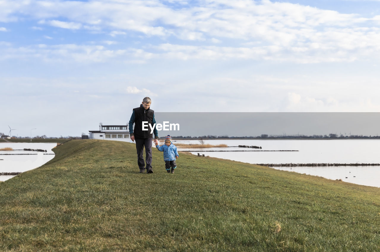 water, sky, grass, cloud - sky, real people, togetherness, lifestyles, nature, two people, adult, land, day, leisure activity, women, full length, plant, family, people, lake, outdoors, positive emotion, daughter