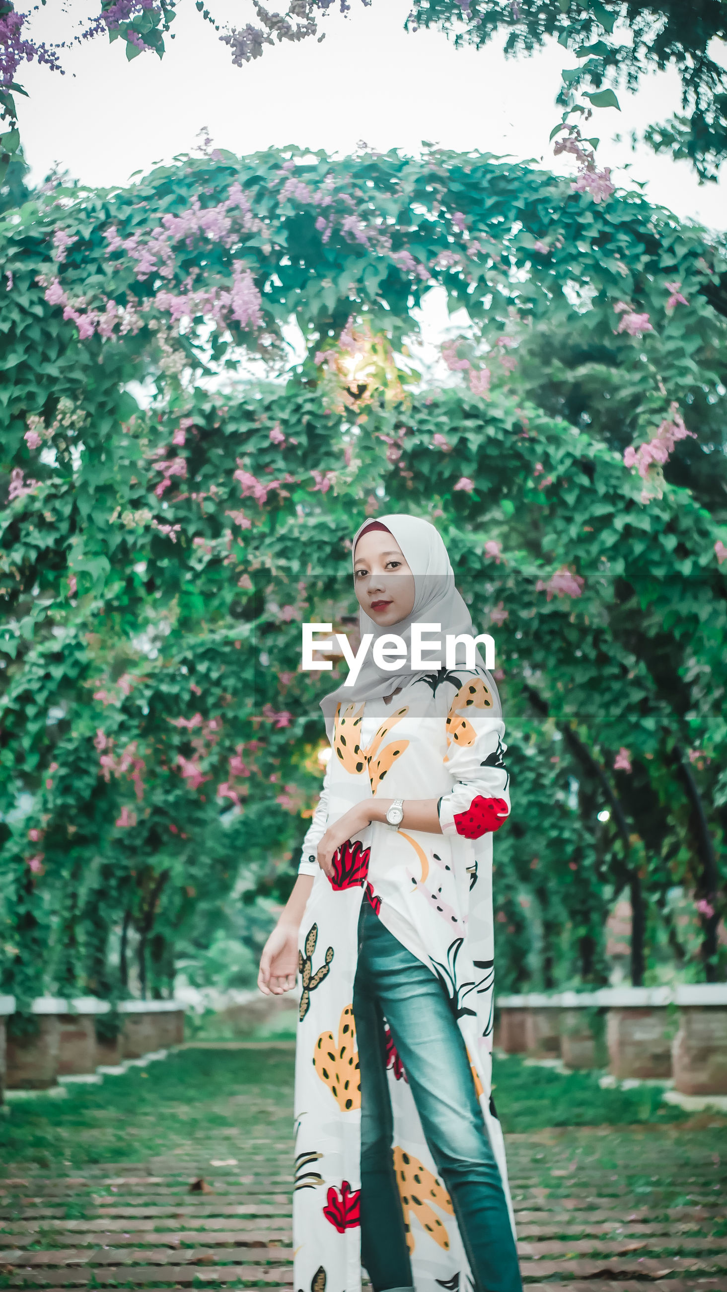 YOUNG WOMAN STANDING BY FLOWER TREE