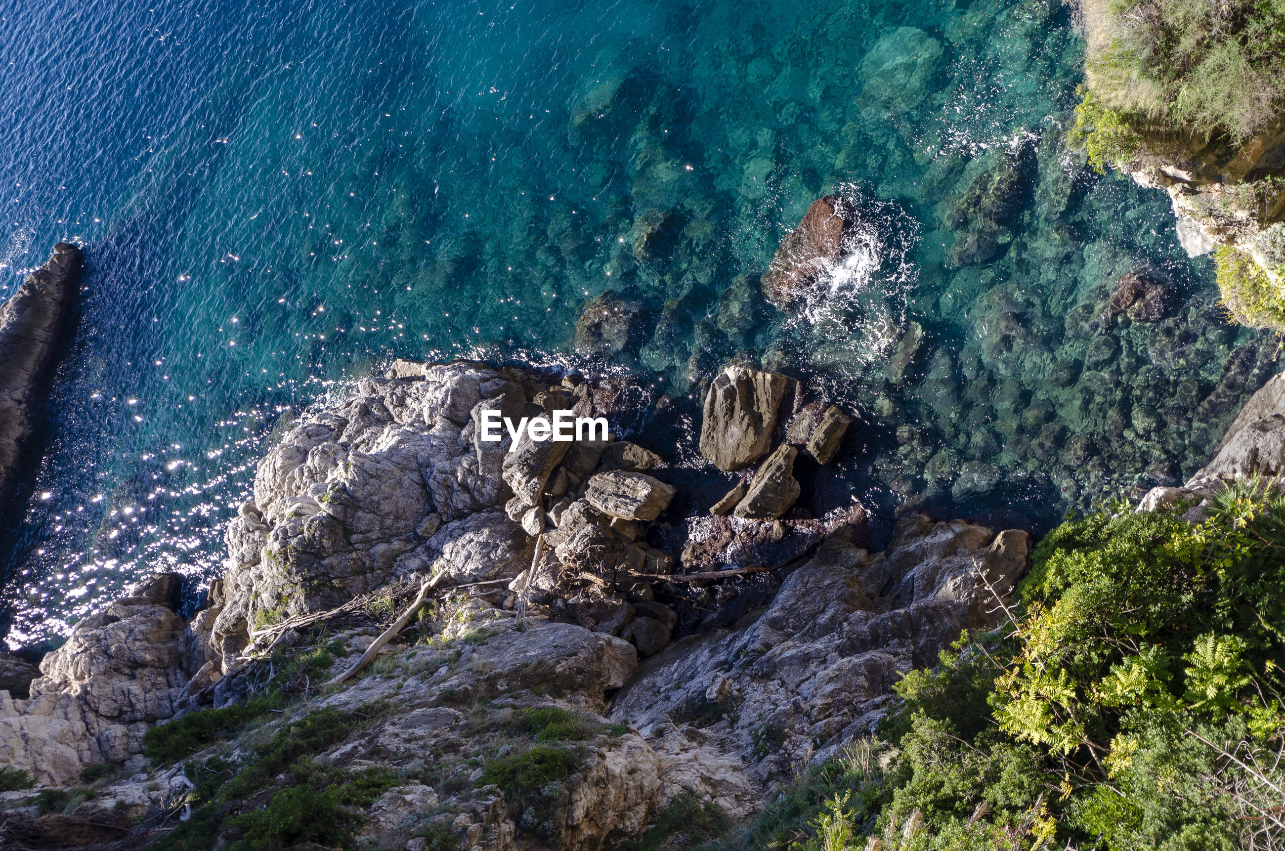 HIGH ANGLE VIEW OF ROCK FORMATION ON SEA