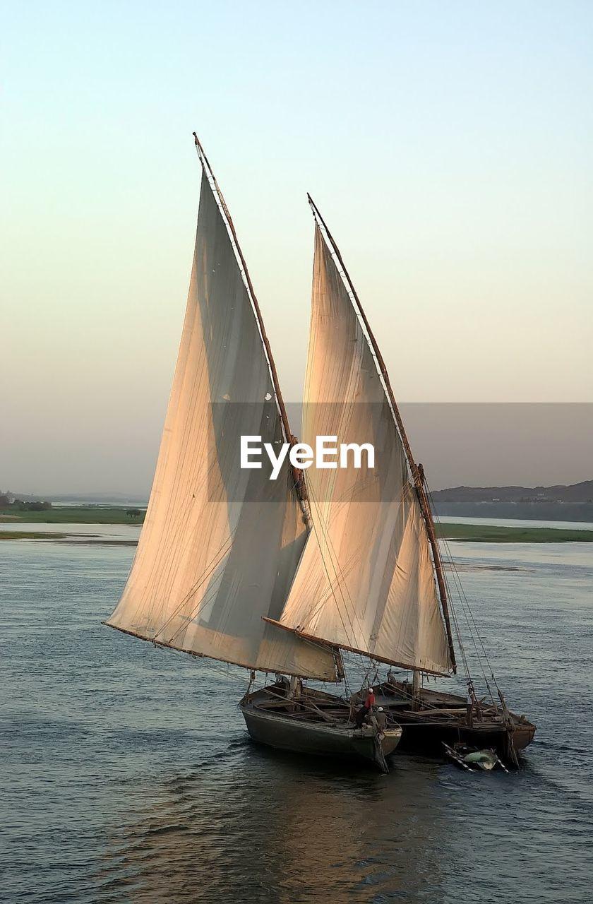 sailboat, nautical vessel, transportation, outdoors, no people, sailing, sea, water, day, sky, sunset, nature, clear sky, horizon over water, sailing ship, tall ship