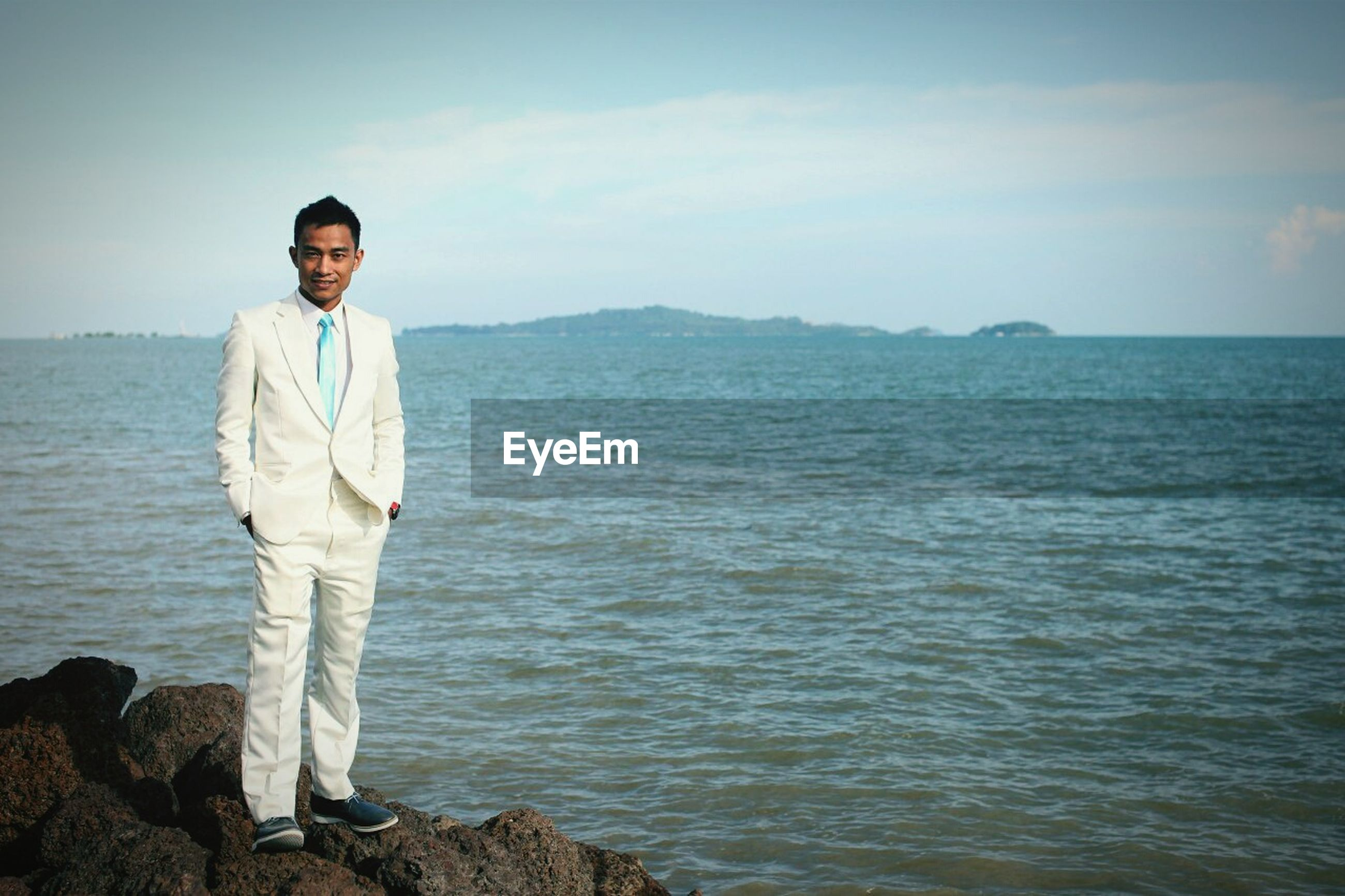 Portrait of well-dressed young man standing on rock by sea