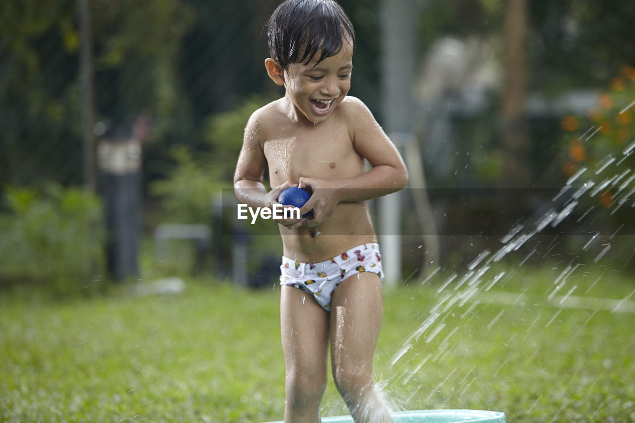 Happy Boy Standing In Bathtub On Grass At Back Yard
