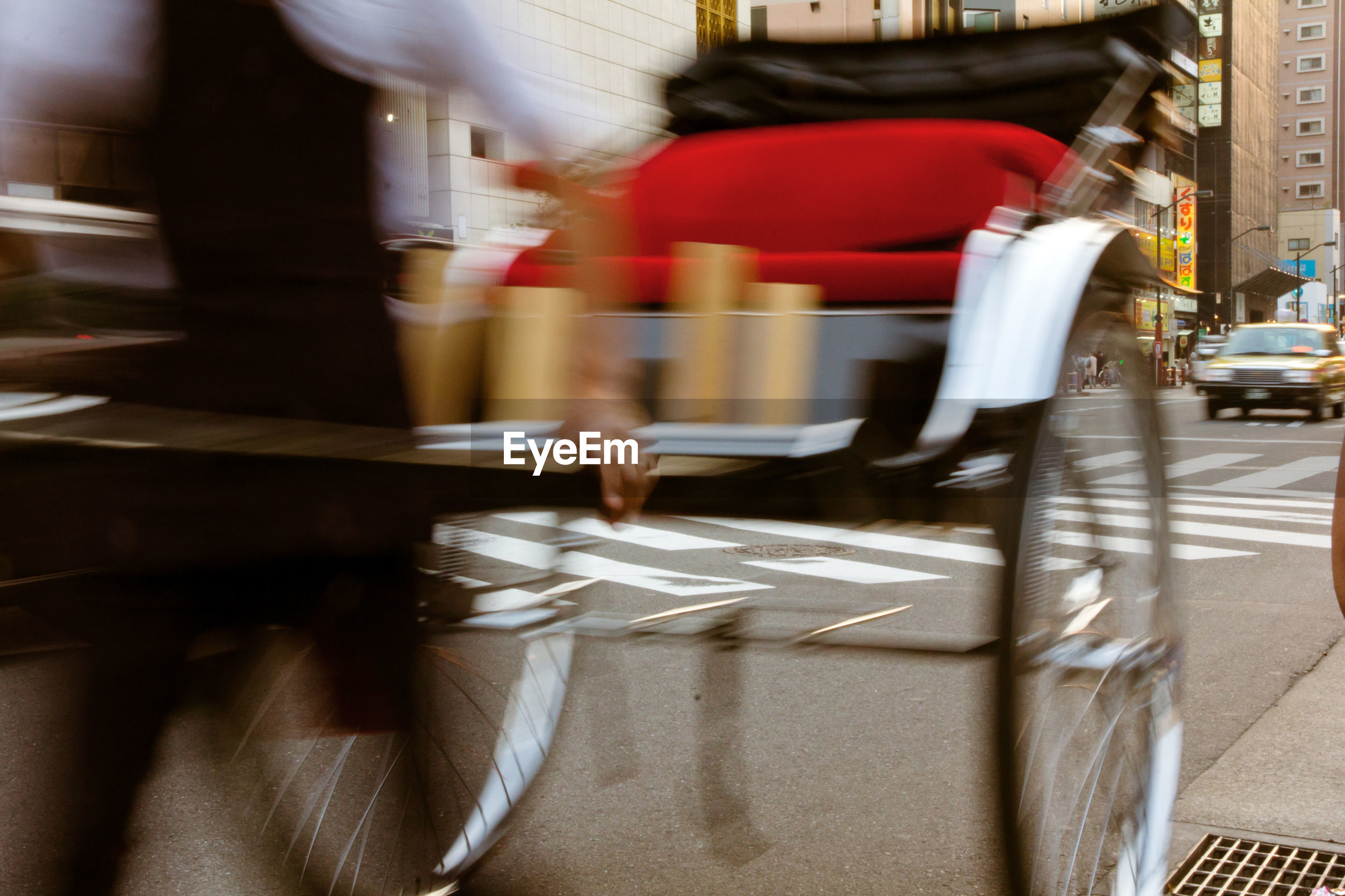 Blurred motion of man with cart walking on road
