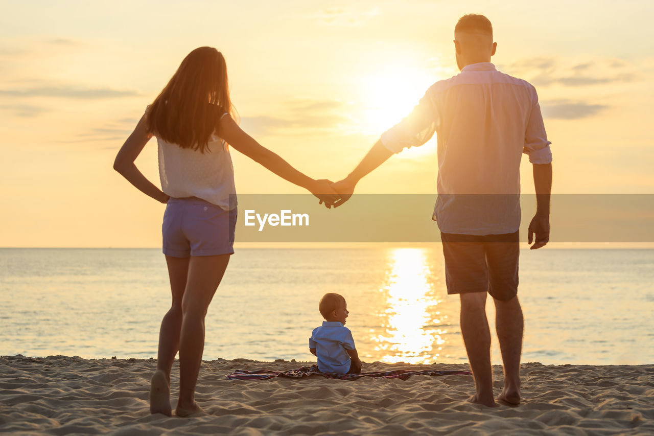 Rear view of parents holding hands while standing by son at beach during sunset