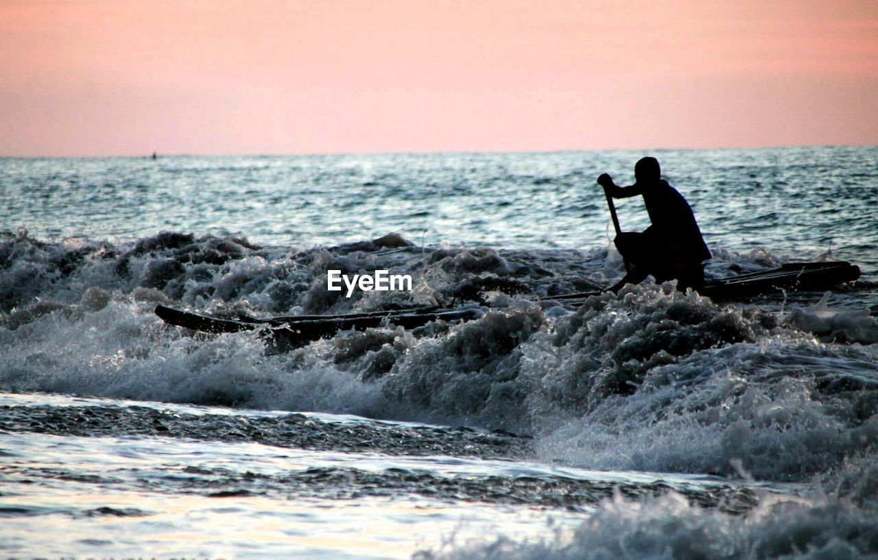 Man Paddling Boat In Sea Against Sky During Sunset