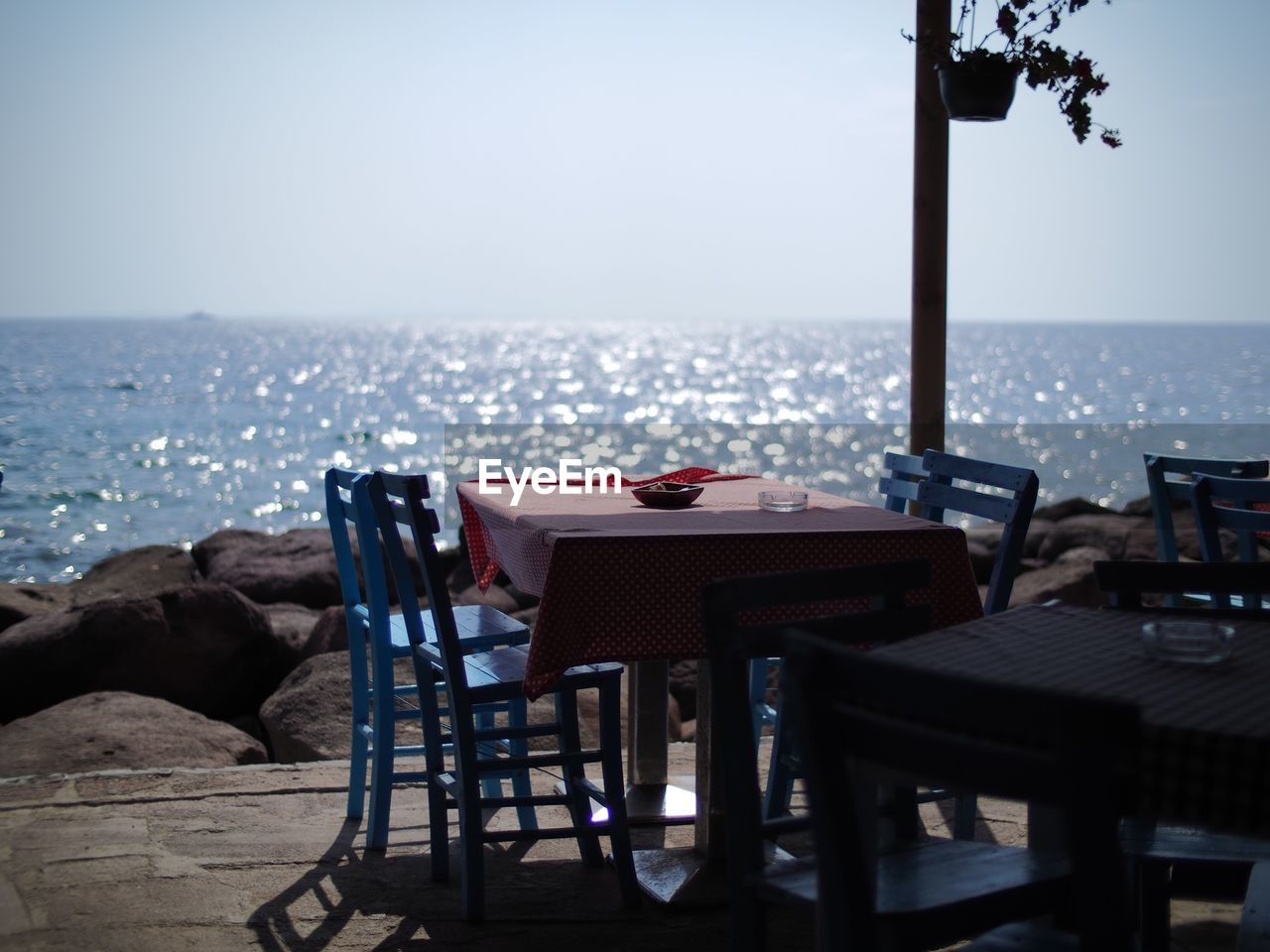 Empty Chairs And Table At Restaurant Against Horizon