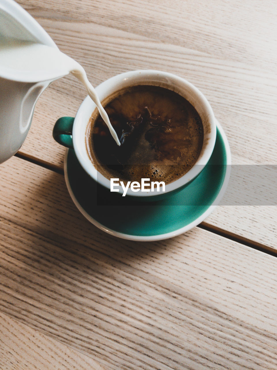 High angle view of milk being poured in black coffee on table