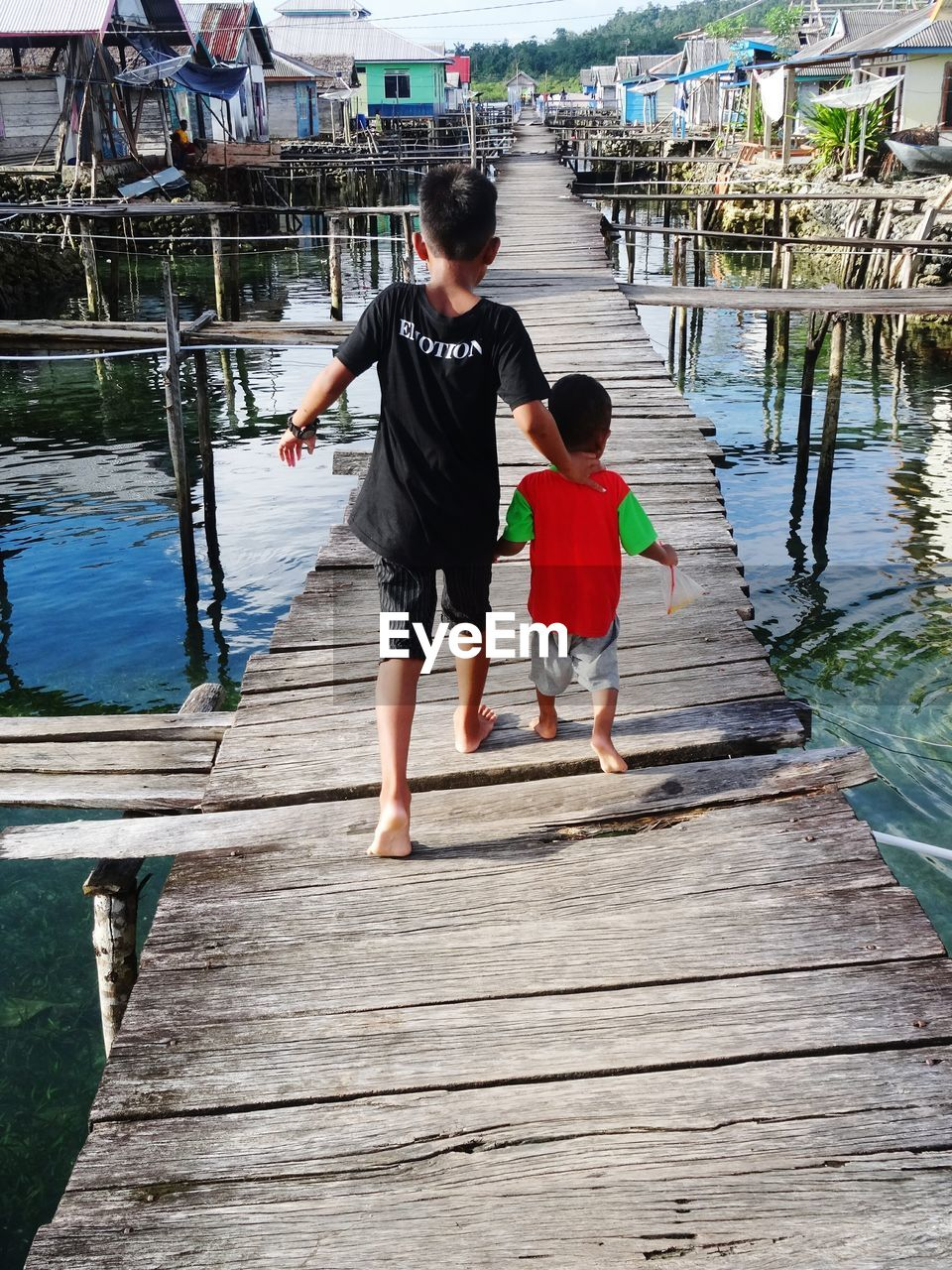 childhood, real people, full length, boys, togetherness, leisure activity, wood - material, outdoors, day, walking, family with one child, lifestyles, water, son, elementary age, girls, vacations, standing, nature, adult, people