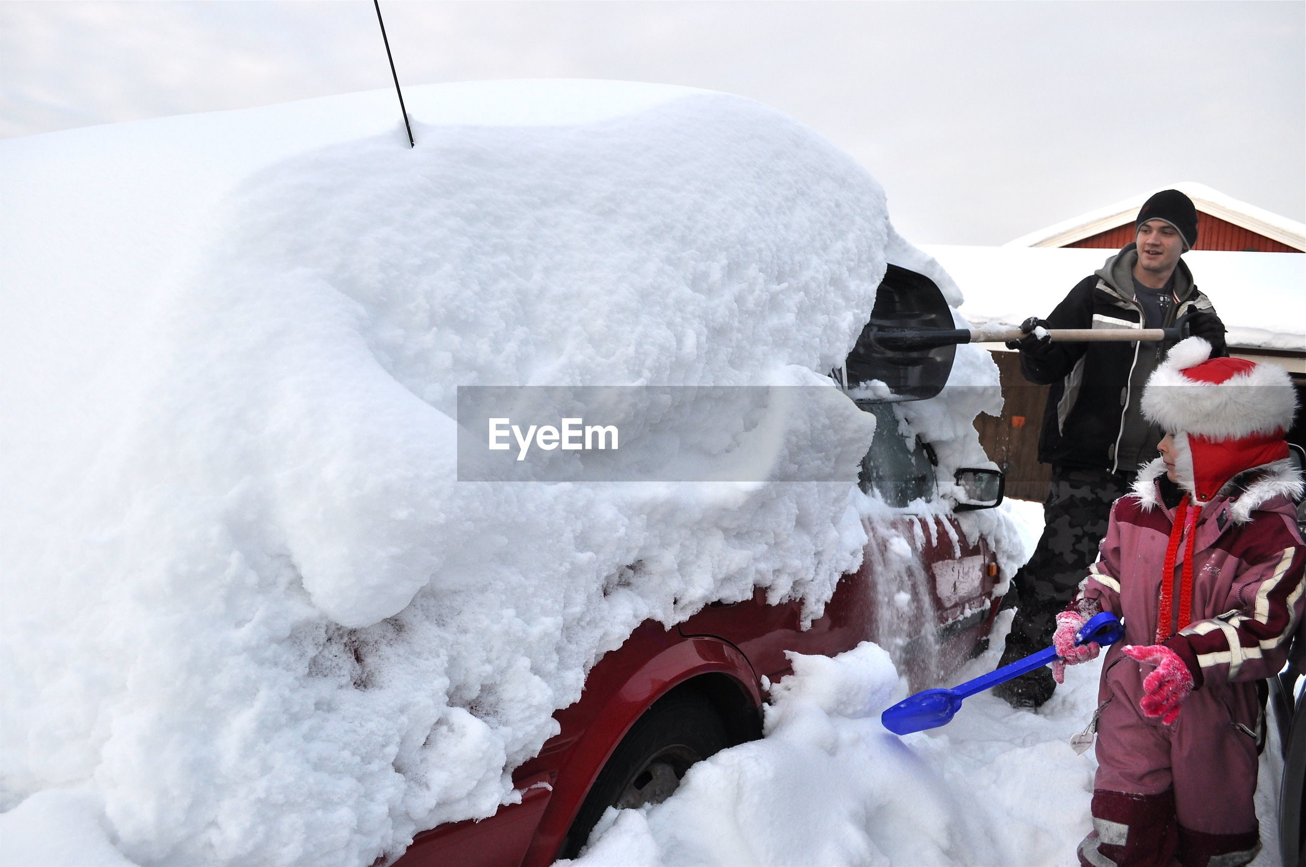 Family cleaning snow on car