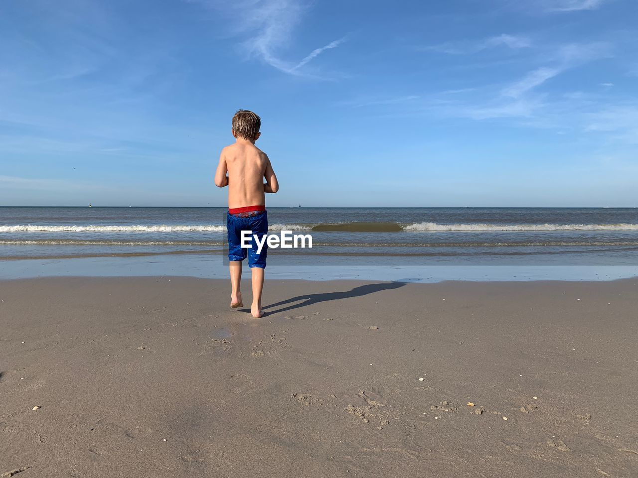 beach, land, sea, water, full length, childhood, real people, males, one person, sky, men, horizon over water, boys, child, leisure activity, rear view, horizon, sand, casual clothing, outdoors, shorts