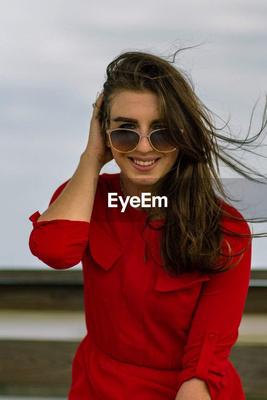 red, one person, real people, leisure activity, lifestyles, glasses, young women, young adult, fashion, focus on foreground, smiling, sunglasses, adult, front view, water, women, sky, hair, hairstyle, outdoors, beautiful woman