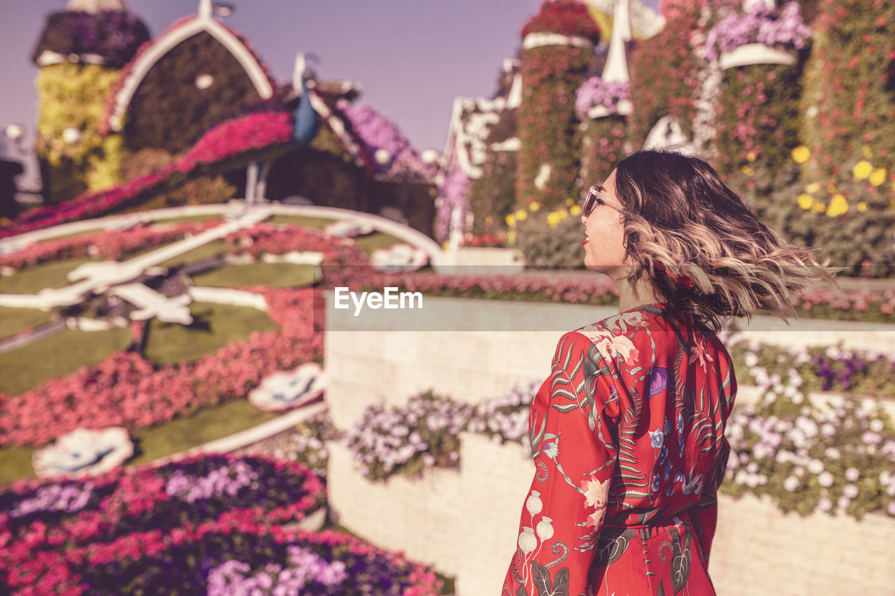 Side View Of Young Woman Tossing Hair In Ornamental Garden