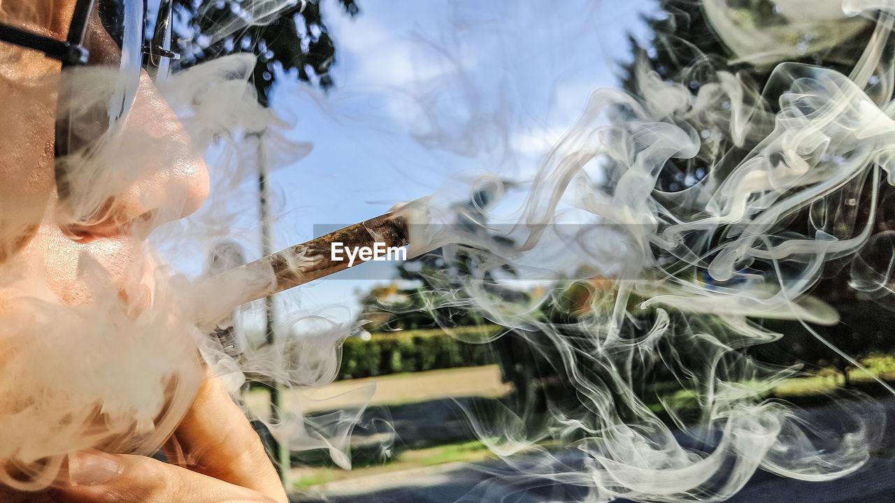 Close-Up Of Man Smoking Marijuana Joint