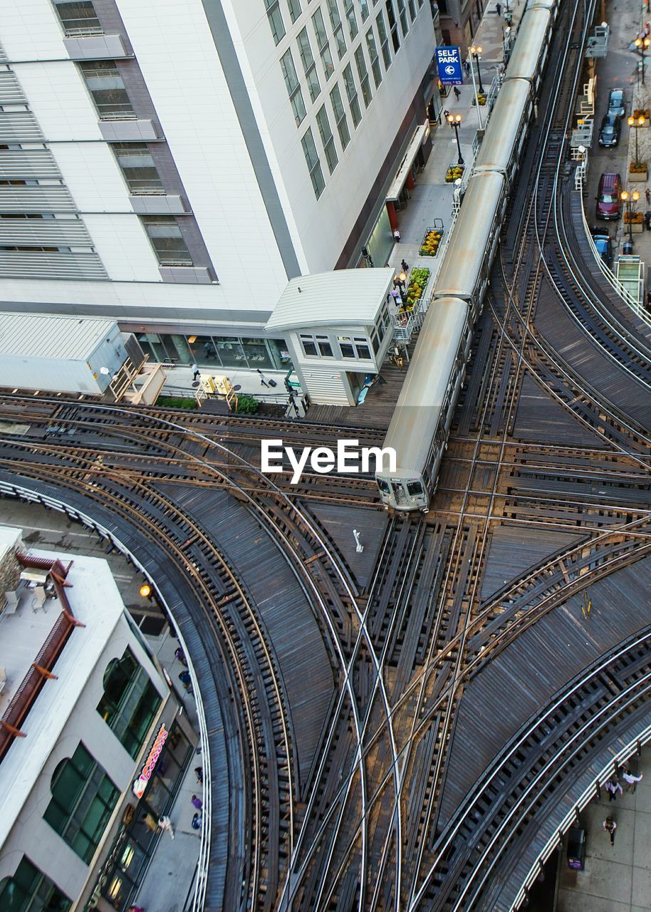architecture, building exterior, built structure, transportation, rail transportation, high angle view, train - vehicle, railroad track, city, public transportation, railroad station, modern, day, mode of transport, outdoors, real people
