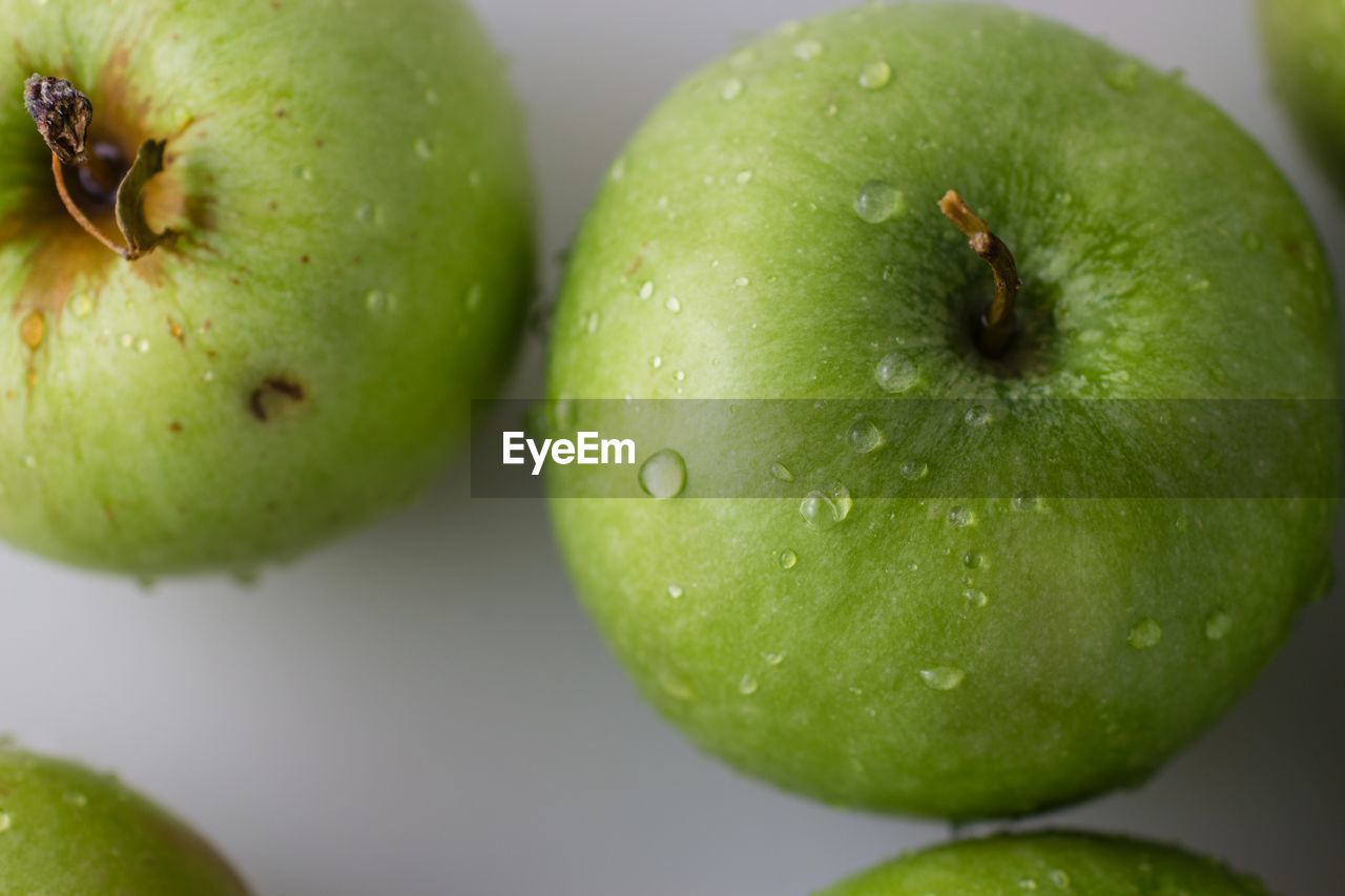 CLOSE-UP OF FRESH APPLE ON GREEN TABLE