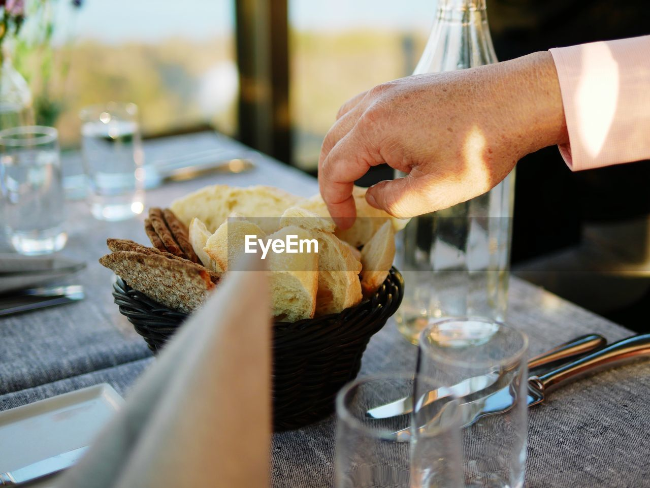 Cropped Hand Having Bread At Table In Restaurant