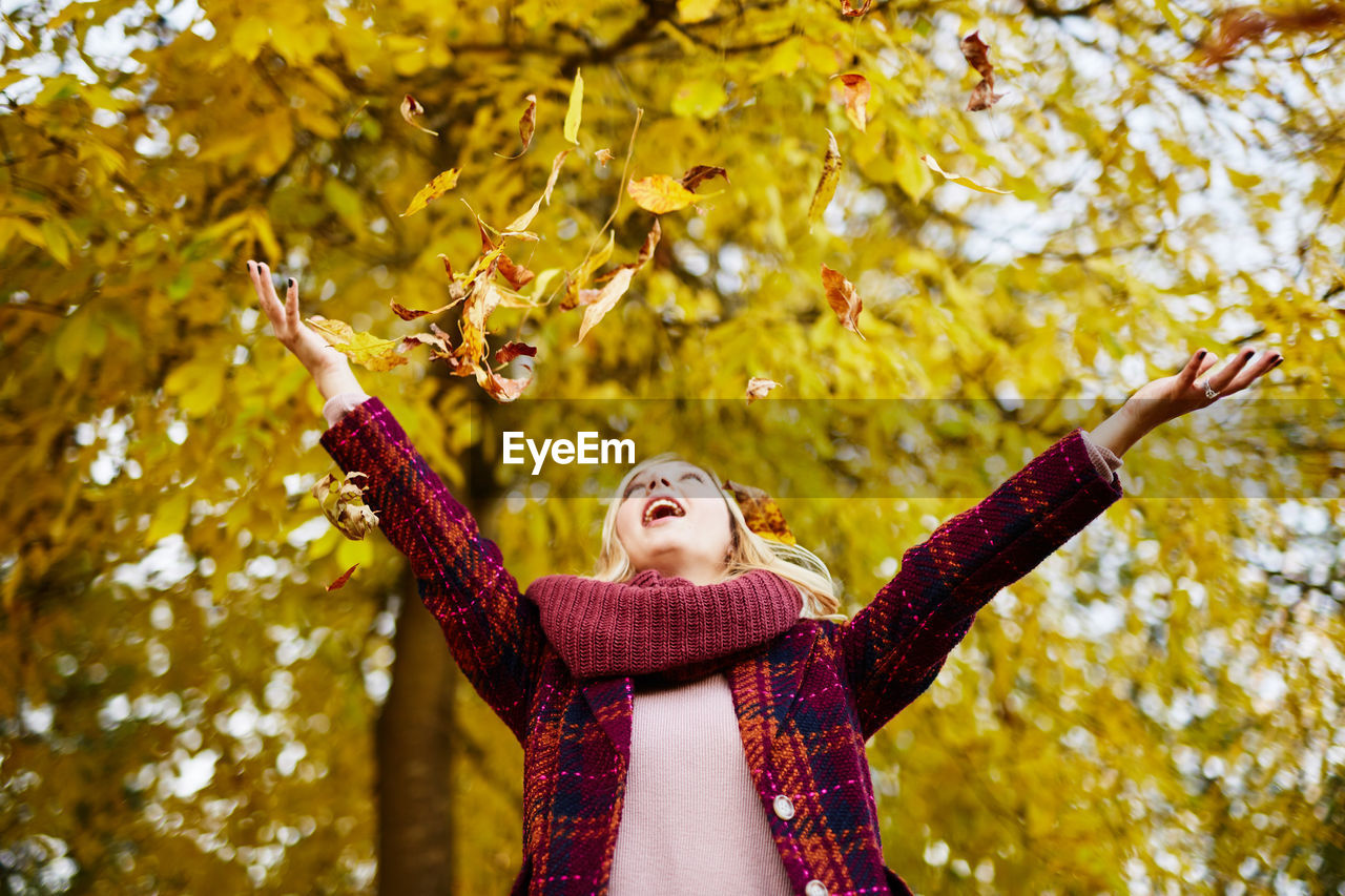 Low Angle View Of Young Woman Playing Against Autumn Tree